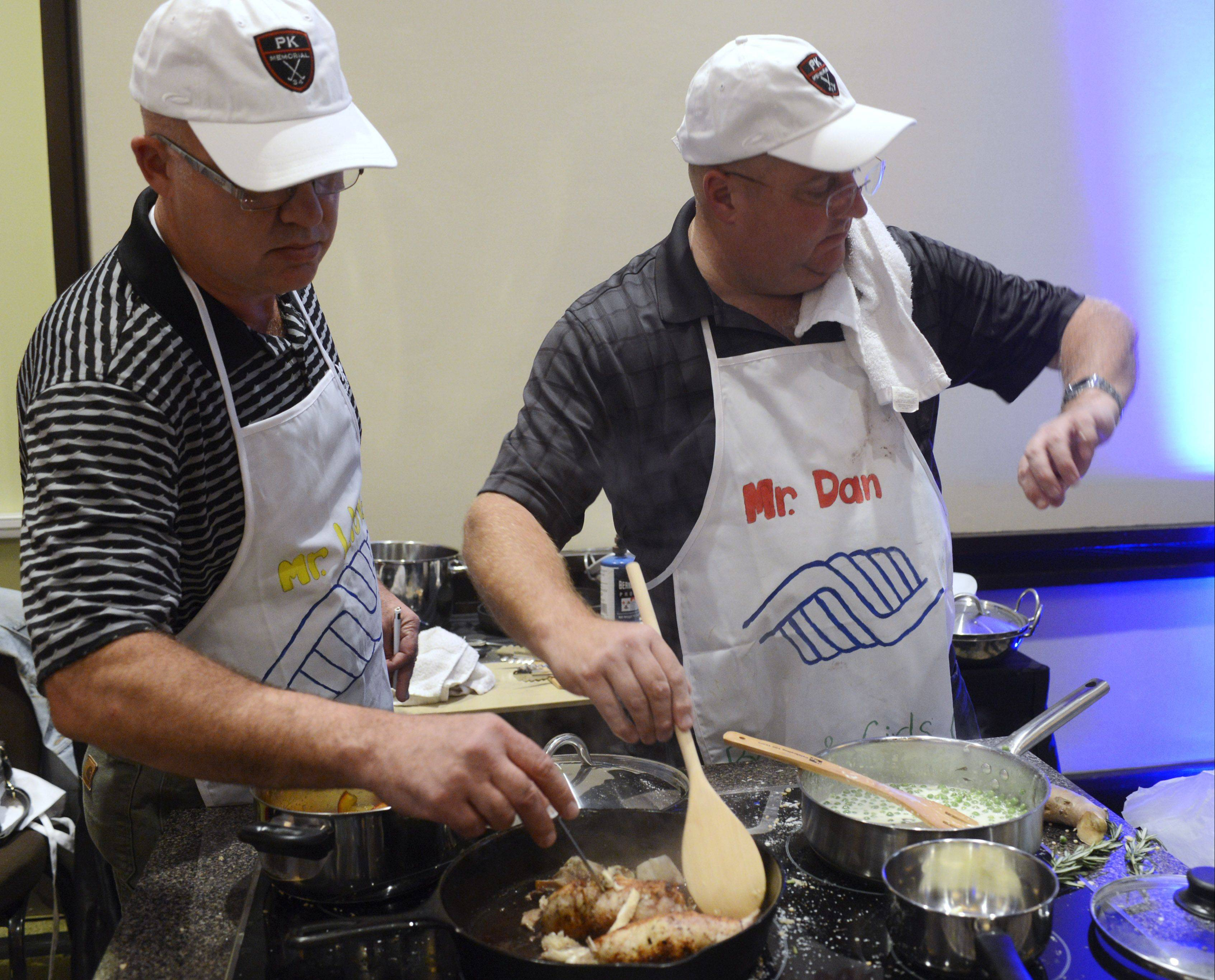 Cook of the Week Challenge contestant Dan Rich of Elgin, right, checks his watch as the deadline nears for him to plate his dish with the cook-off finals at the Hyatt Regency Schaumburg.
