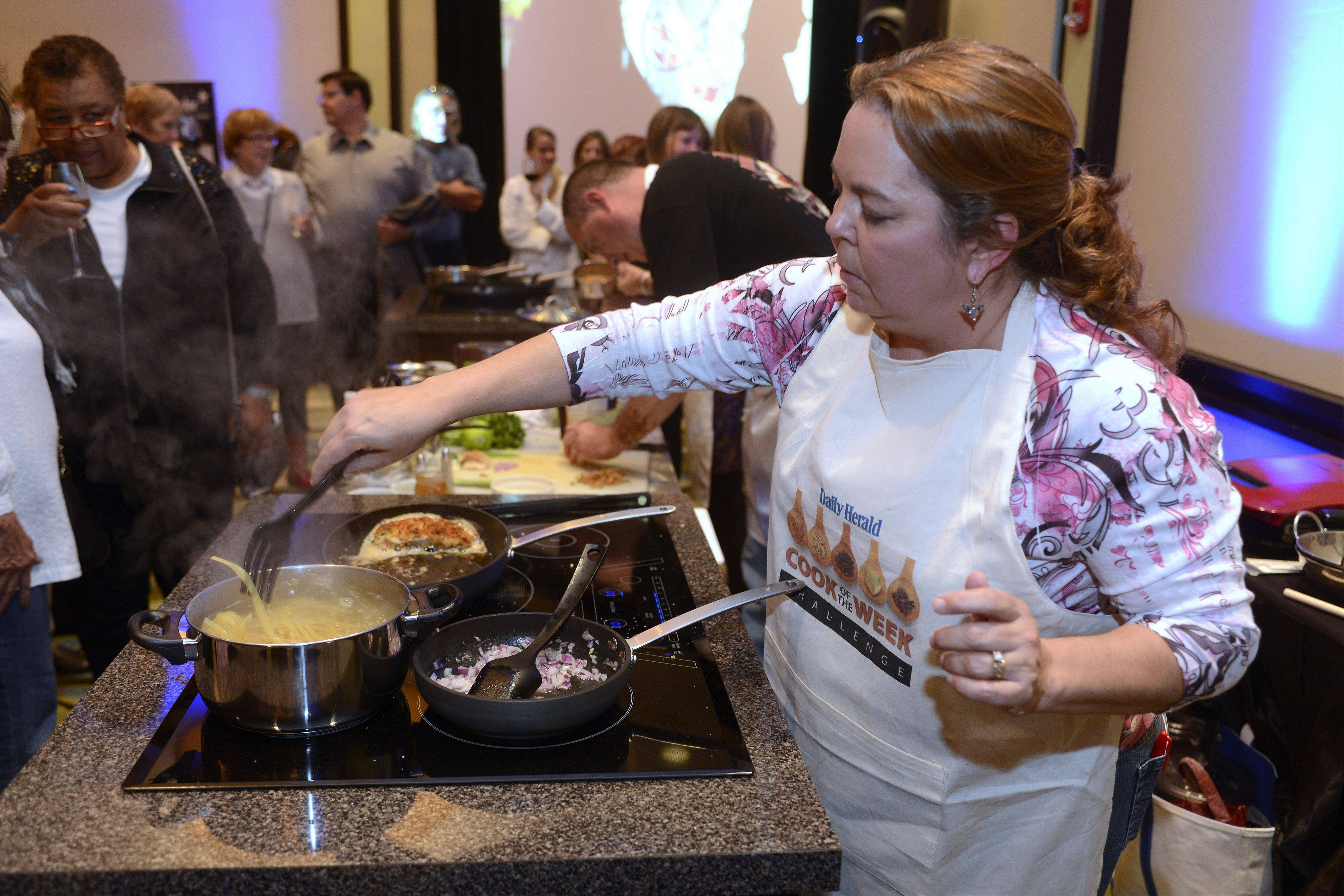 Lori Wiktorek of Aurora puts pasta on to boil as she prepares her dish at the Daily Herald Cook of the Week Challenge Cook-off.