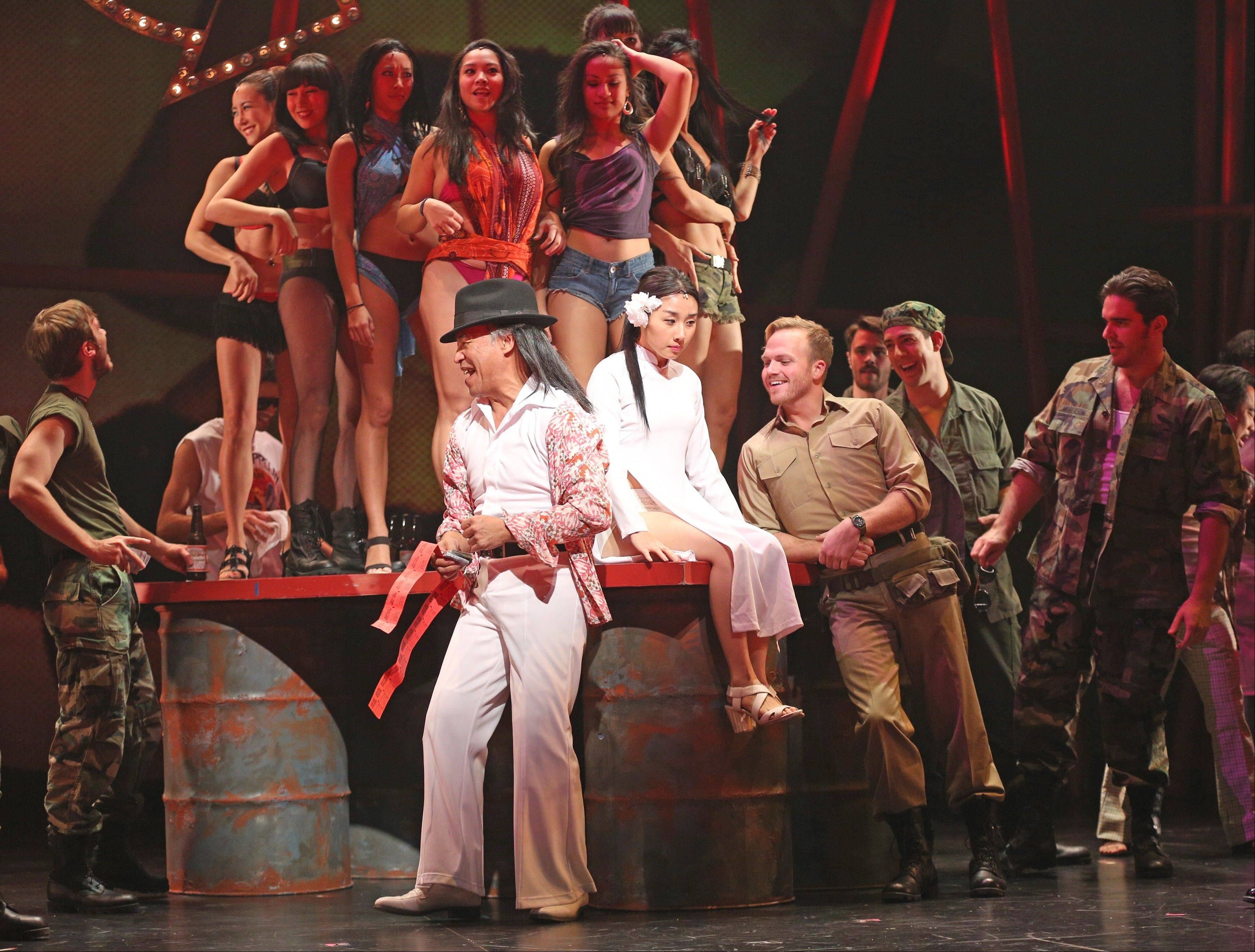 "The Engineer (Joseph Anthony Foronda, center) sells raffle tickets to American soldiers for his Miss Saigon bar girl beauty contest in the Paramount Theatre's production of the Vietnam War-era Broadway musical ""Miss Saigon."""