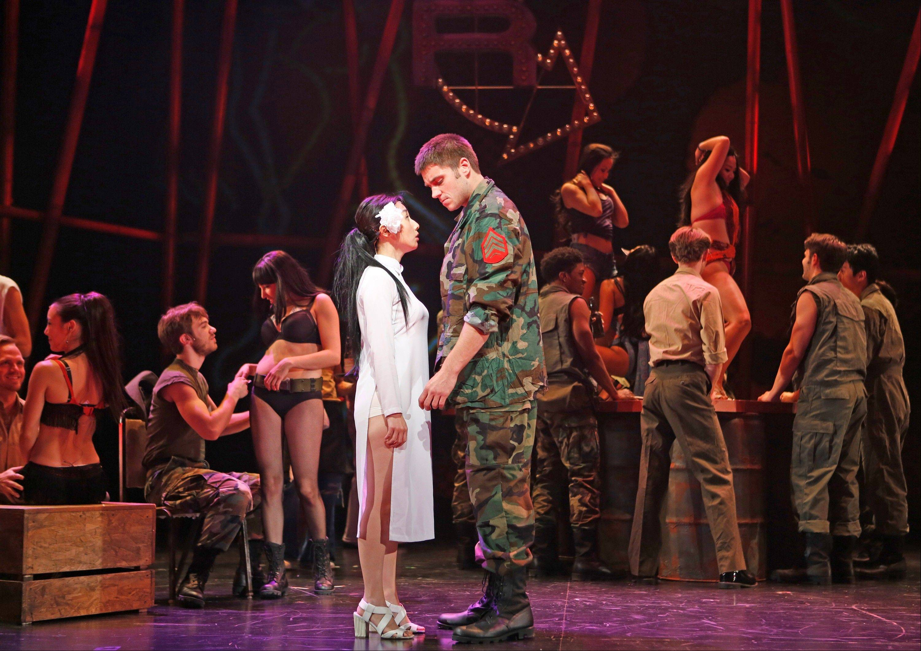 "The recently orphaned Kim (Shawna Haeji Shin) is paired with the American soldier Chris (Brandon Moorhead) in a seedy bar in the Paramount Theatre's production of the Broadway musical ""Miss Saigon,"" playing now through Sunday, Nov. 24, in Aurora."