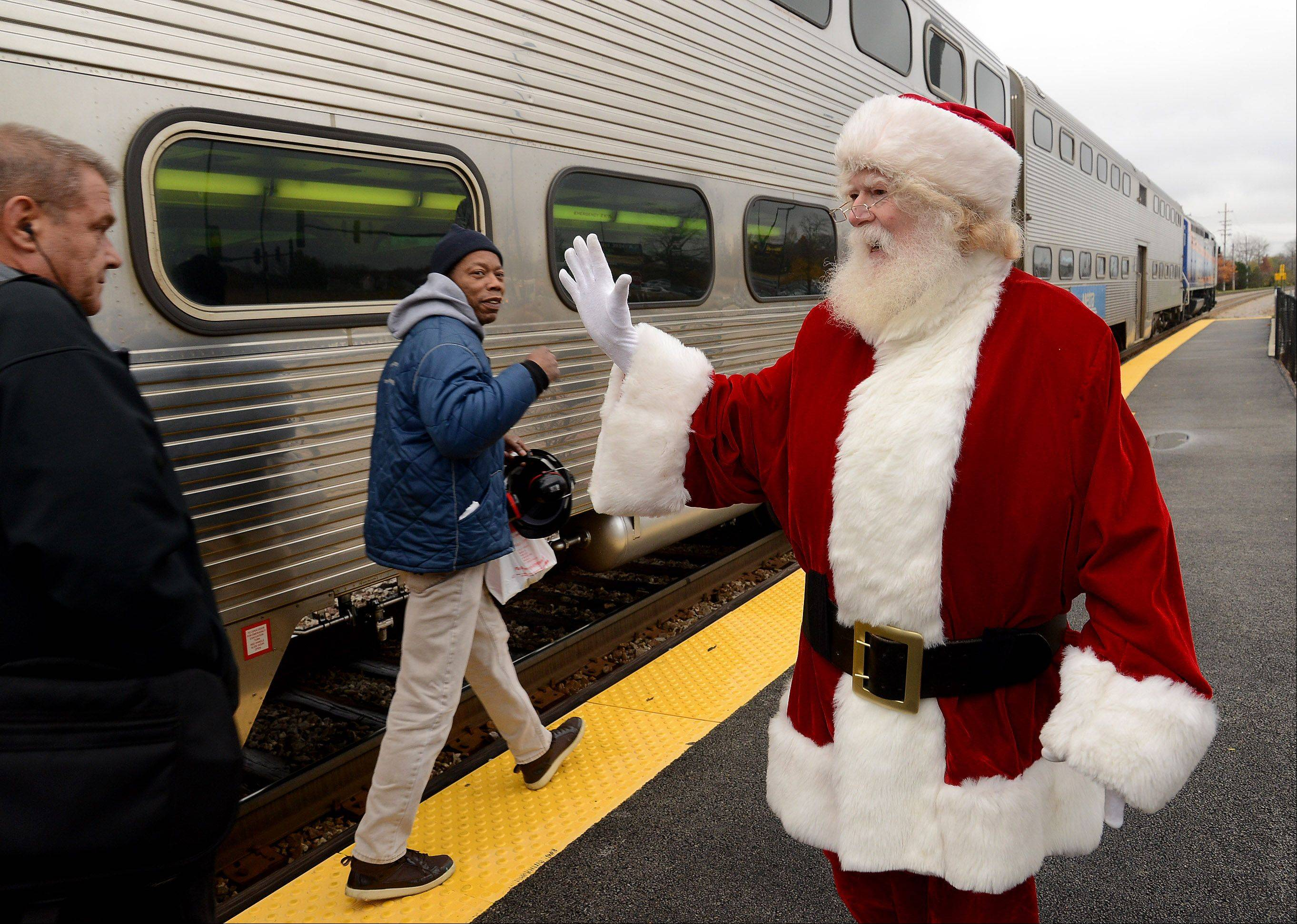 Streamwood Santa John Sullivan greets passengers at the Hanover Park train station Wednesday.