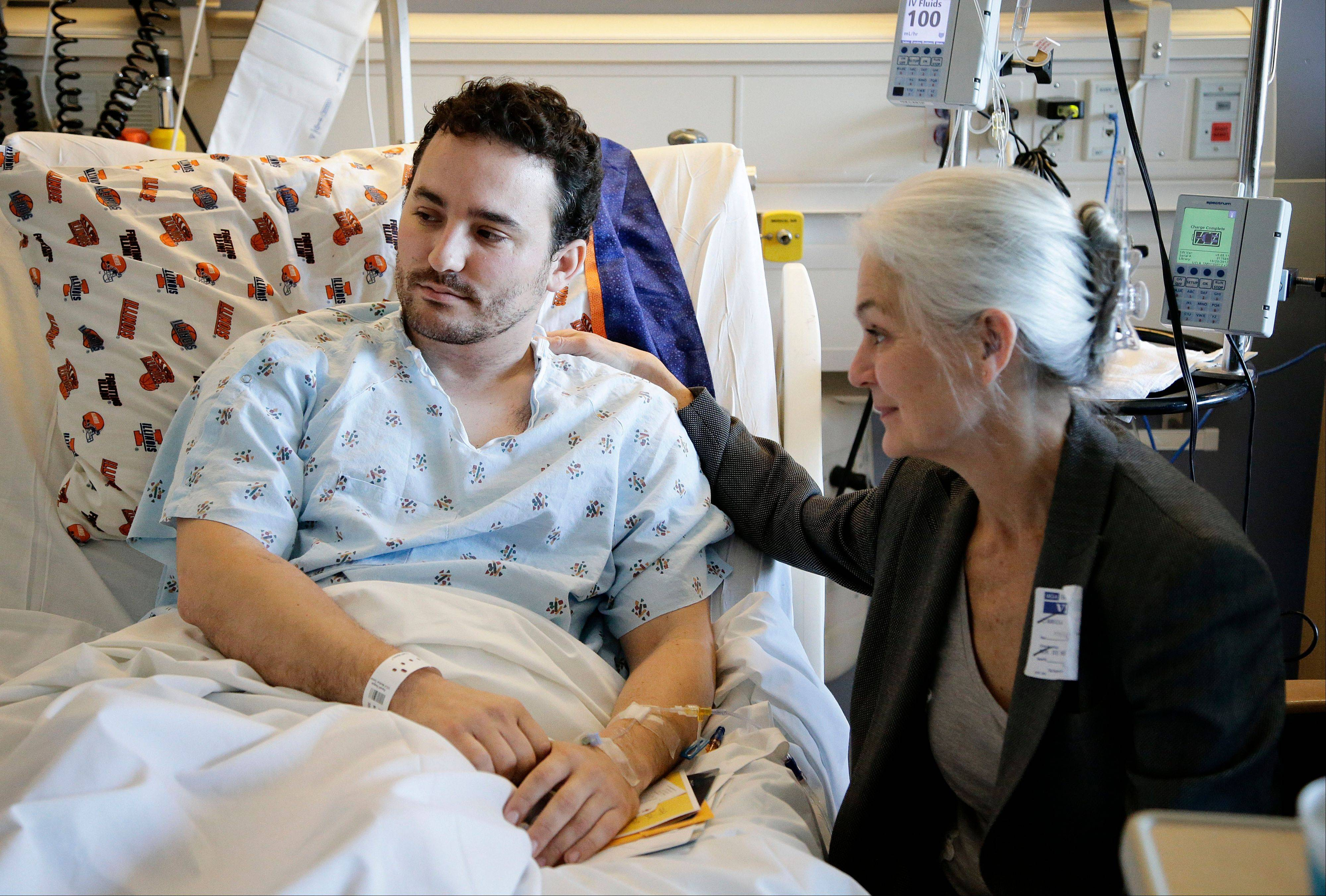 Judy Flaherty, right, comforts her son Brian Ludmer, who was the lone civilian wounded by gunfire in the shooting rampage at Los Angeles International Airport Friday, Nov. 1, 2013.