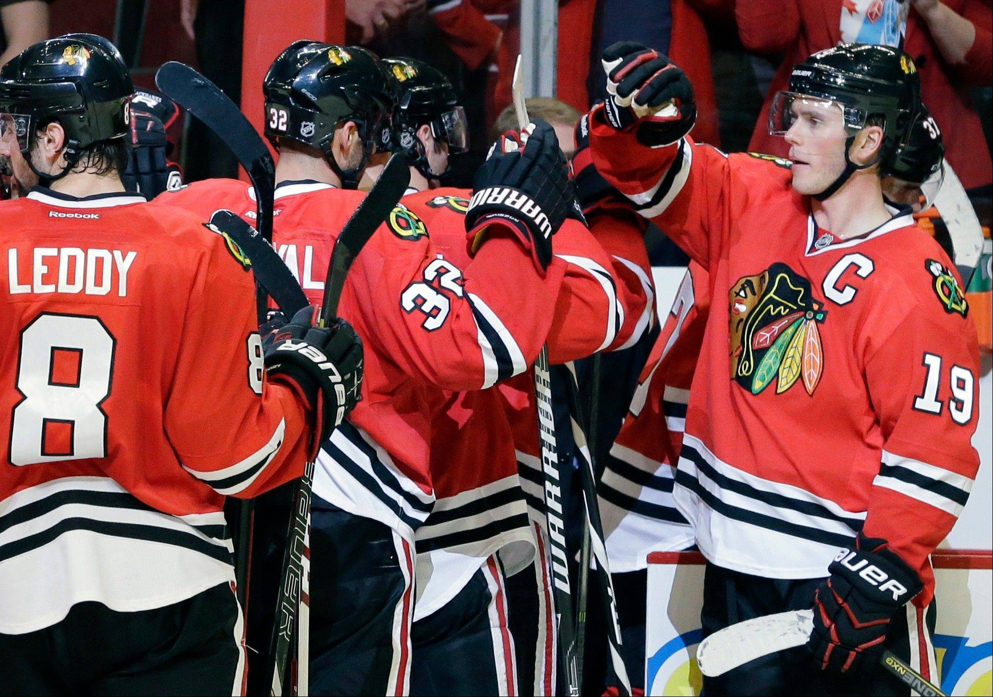 Chicago Blackhawks' Jonathan Toews (19), right, celebrates with teammates after the Blackhawks defeated the Winnipeg Jets 4-1 in an NHL hockey game in Chicago, Wednesday, Nov. 6, 2013.