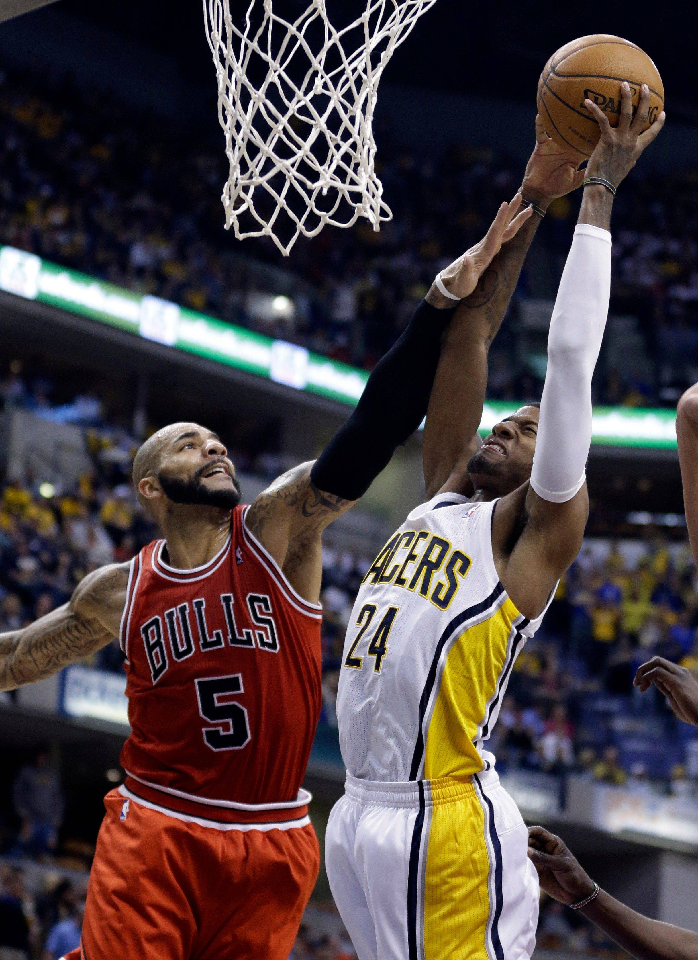Bulls forward Carlos Boozer, left, fouls Indiana Pacers forward Paul George as he shoots in the second half of an NBA basketball game in Indianapolis, Wednesday, Nov. 6, 2013. The Pacers defeated the Bulls 97-80.