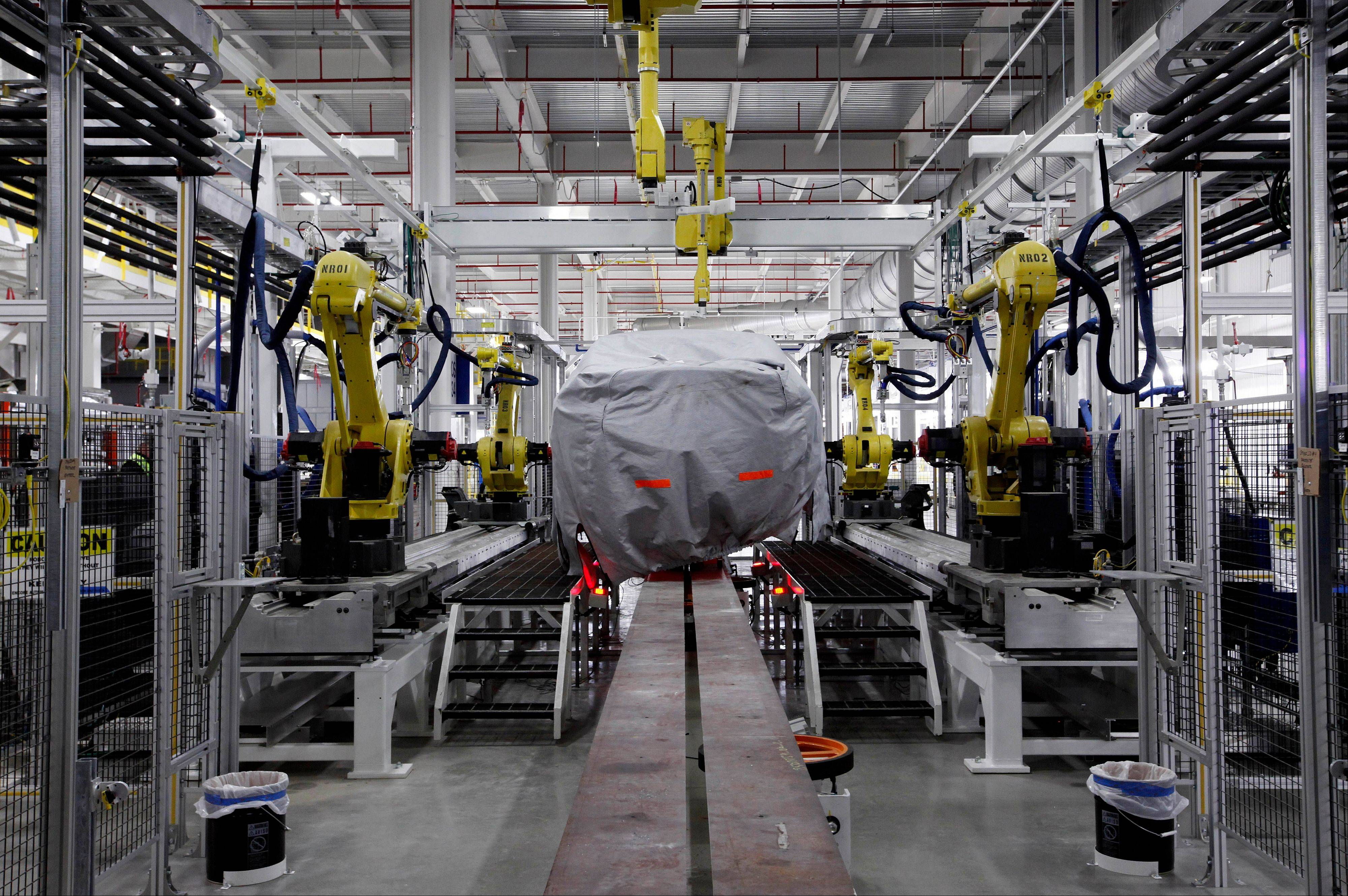 A covered vehicle sits in part of the new paint shop at Chrysler�s Sterling Heights Assembly Plant in Sterling Heights, Mich.