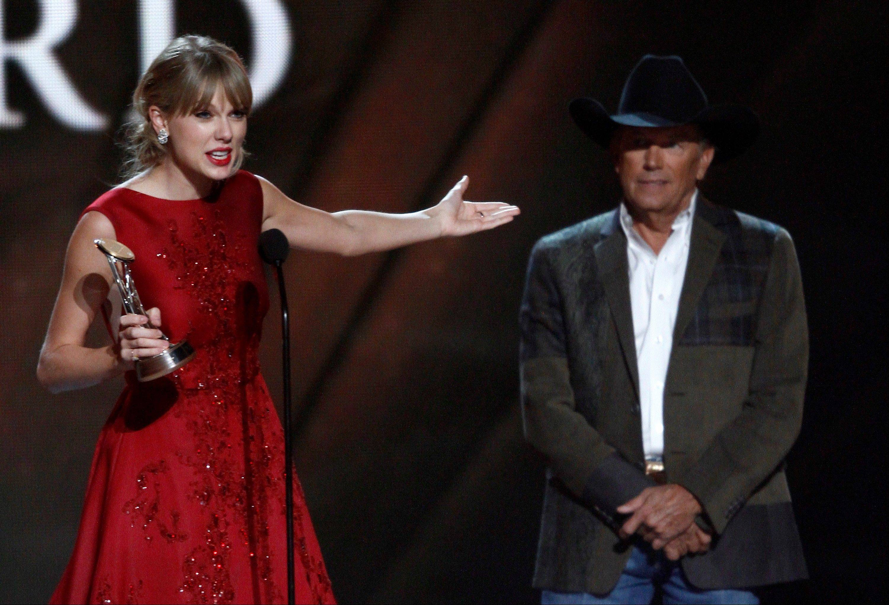 Taylor Swift accepts the Pinnacle award Looking on at right is presenter George Strait.
