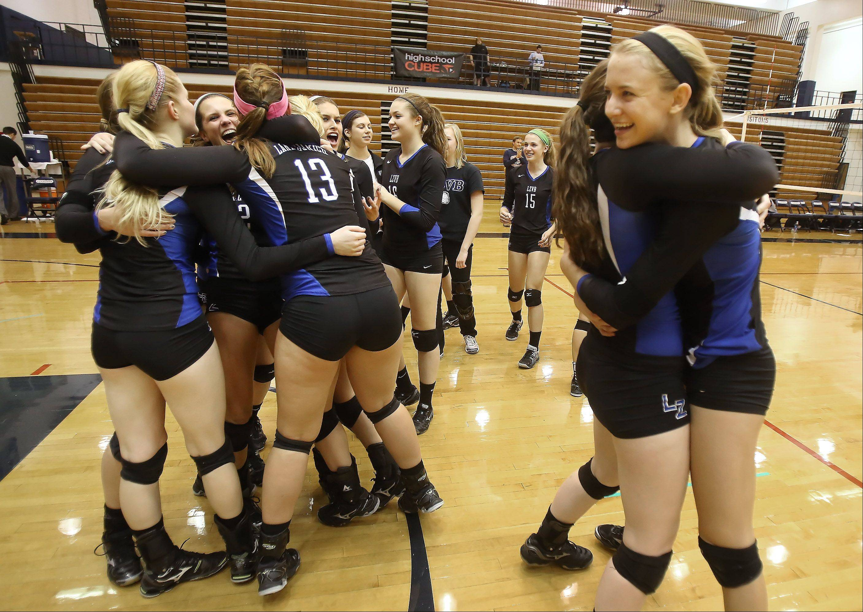 Gilbert R. Boucher II/gboucher@dailyherald.com Lake Zurich players Kristen Walding, right, and Natalie Corrigan hug as they celebrate with teammates after winning the Class 4A volleyball sectional final at Conant High School Thursday and defeating Stevenson High School.