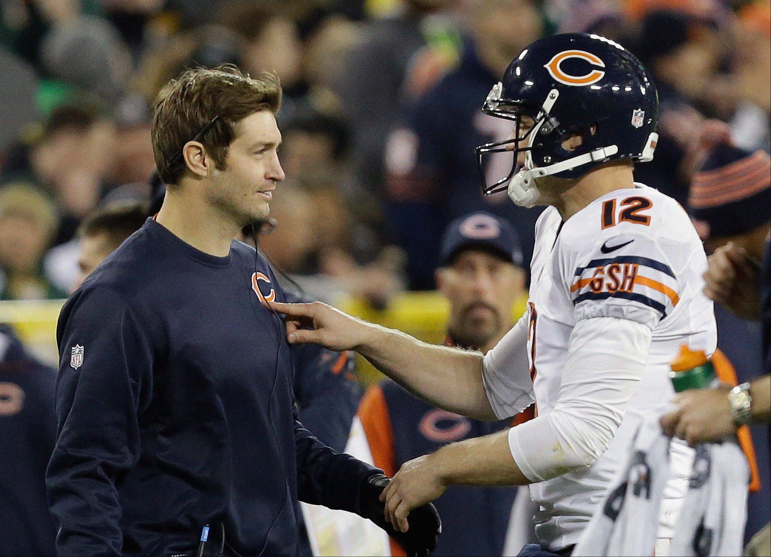 "Josh McCown (12) talks to Jay Cutler during the first half of the Bears' victory over Green Bay on Monday. Cutler hopes to play Sunday against the Lions, but doctors must clear him to play. ""There is no gray area in this decision,"" said Bears coach Marc Trestman."