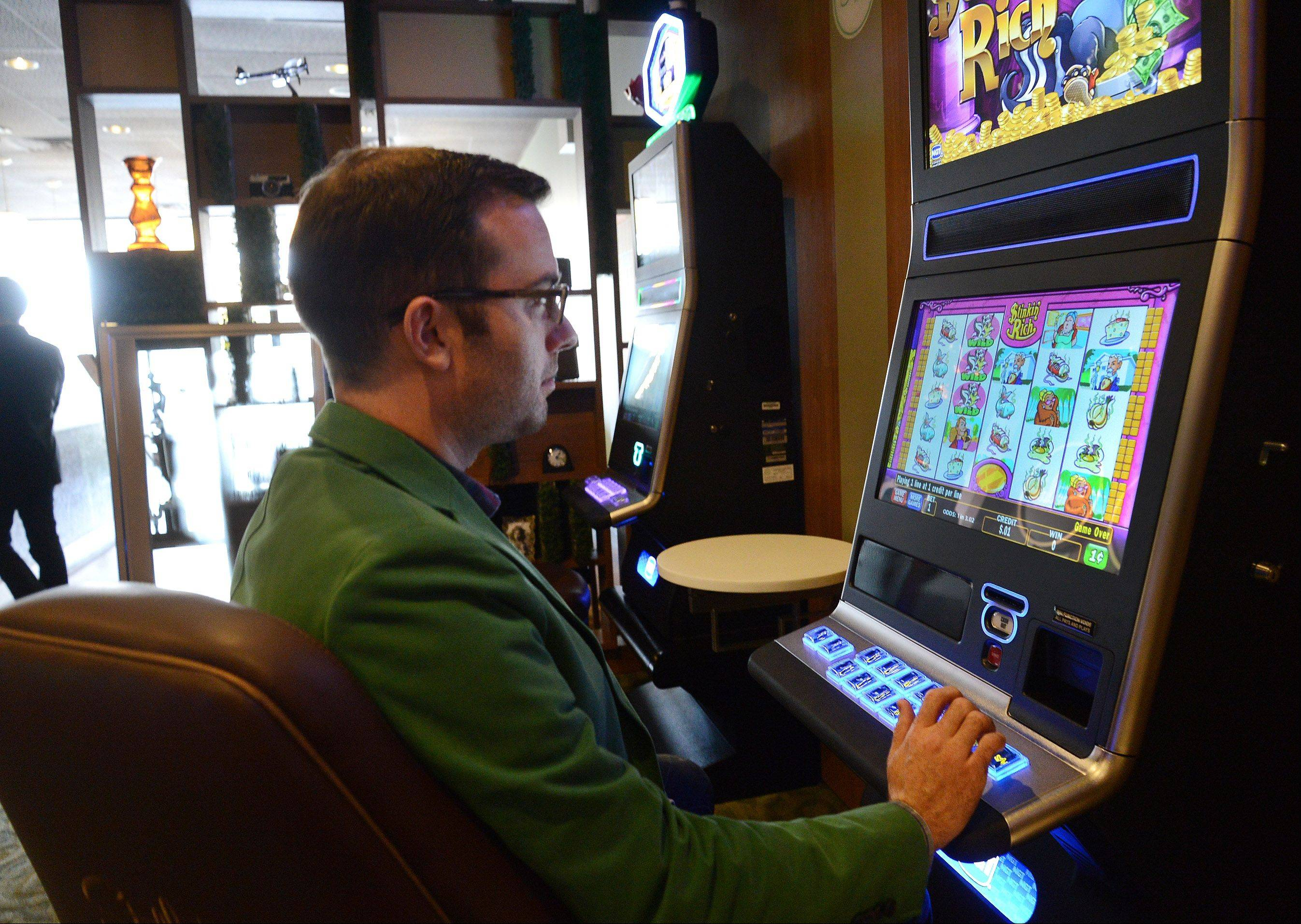 Area Manager Brian Wilson tries out one of the video gaming machines at Stella's, a new bar that opened in Hoffman Estates Thursday.