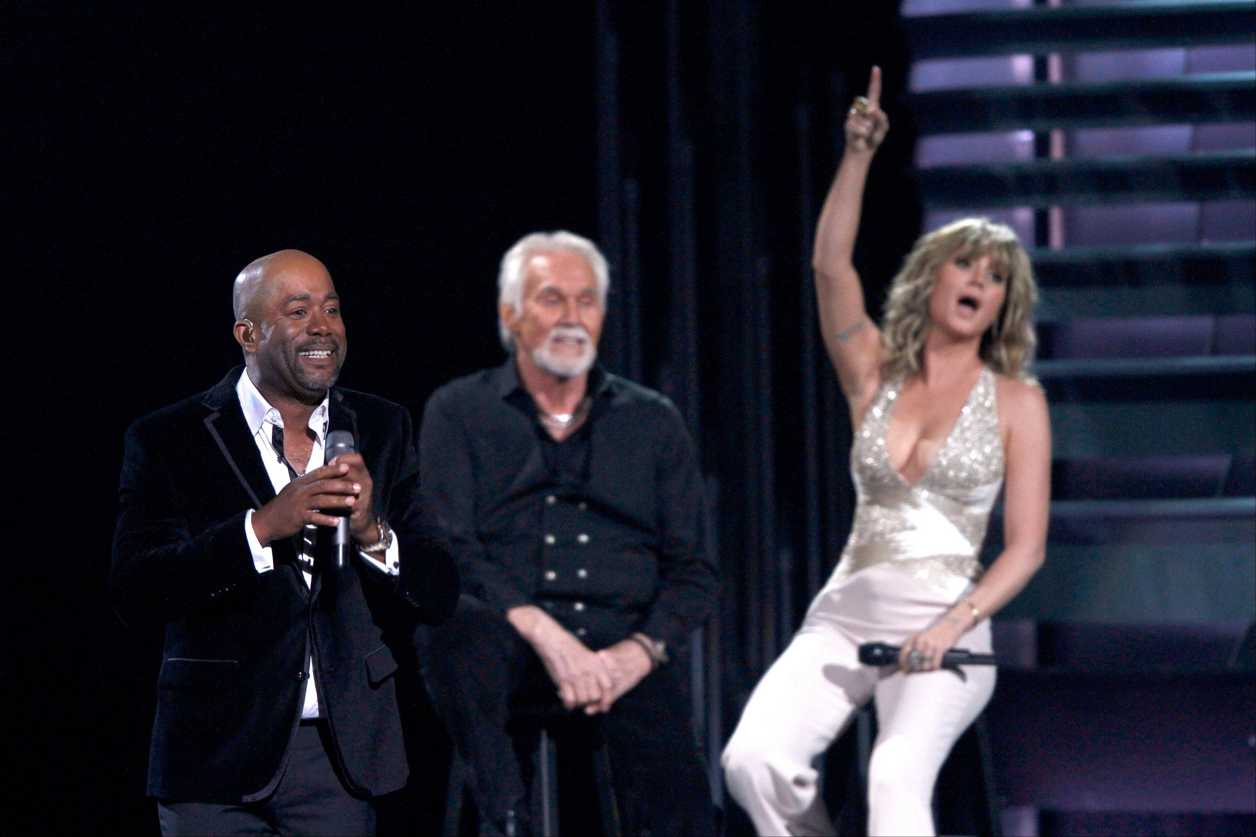 "Darius Rucker sings ""The Gambler"" at the 47th annual CMA Awards at Bridgestone Arena on Wednesday, Nov. 6, 2013, in Nashville, Tenn. In background from second right are Kenny Rogers and Jennifer Nettles. Rogers was the recipient of the Willie Nelson Lifetime Achievement Award."