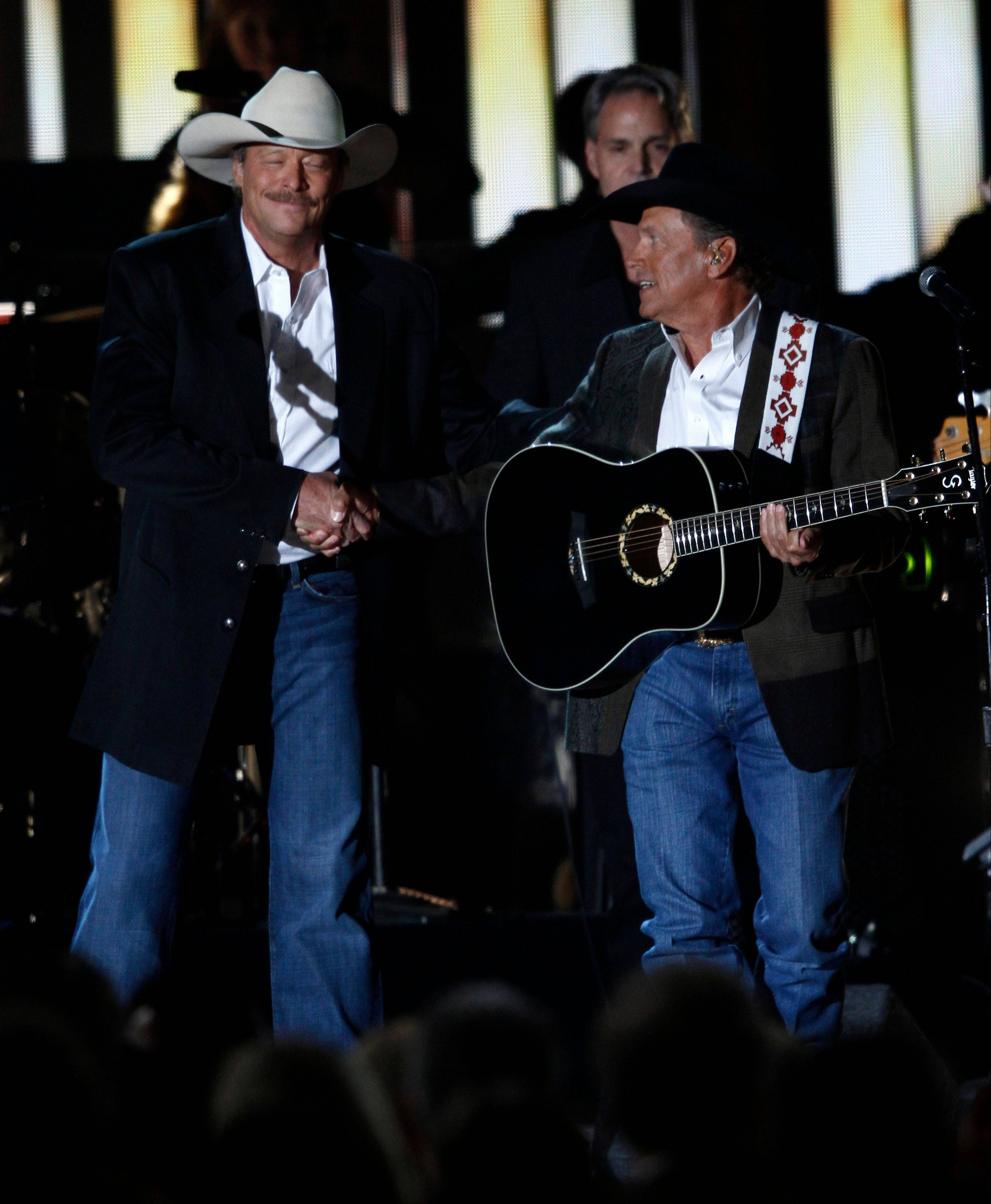 Alan Jackson, left, and George Strait shake hands after paying tribute to George Jones.