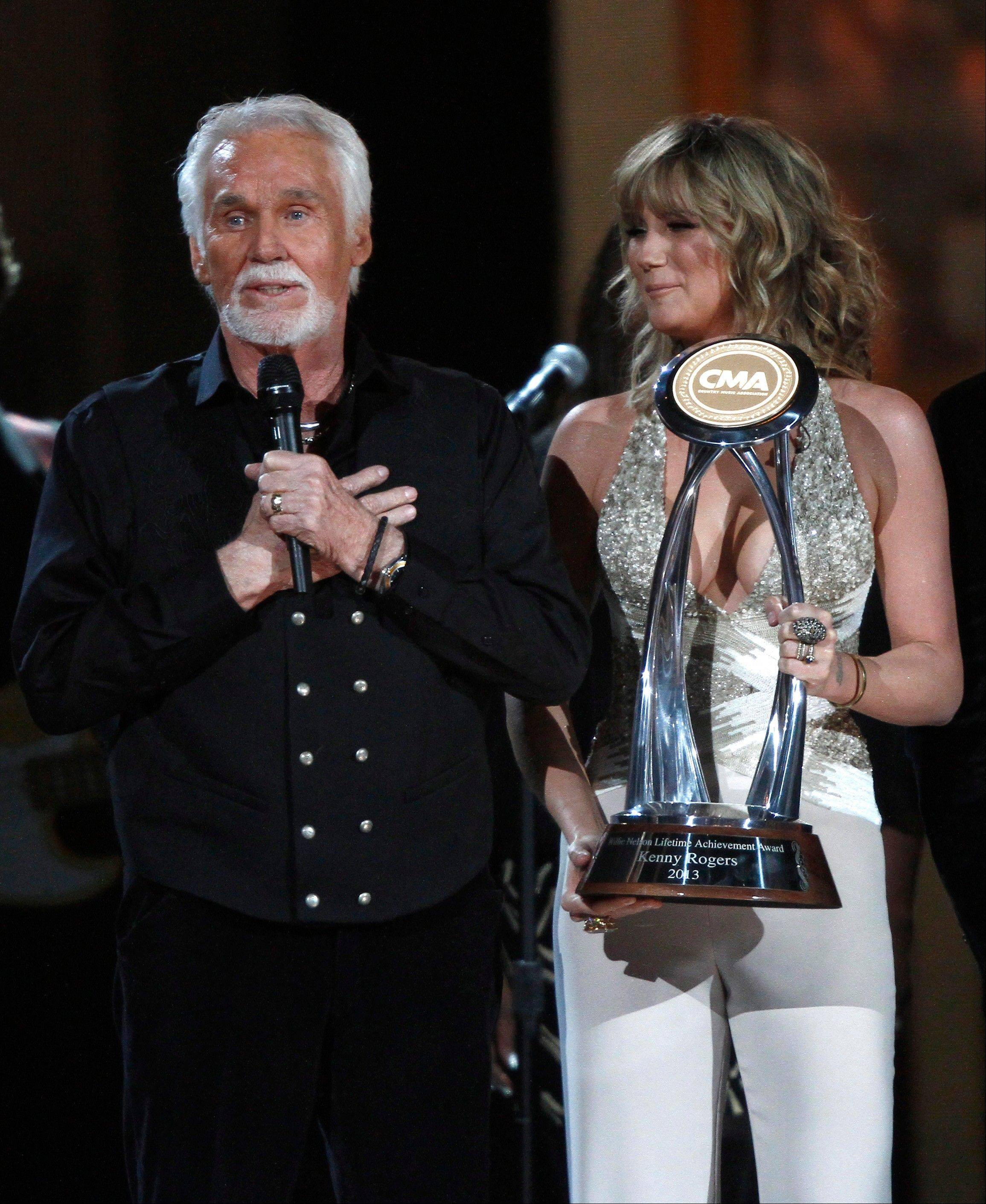 Kenny Rogers, left, accepts the Willie Nelson Lifetime Achievement Award at the 47th annual CMA Awards at Bridgestone Arena on Wednesday, Nov. 6, 2013, in Nashville, Tenn. In background right is Jennifer Nettles.