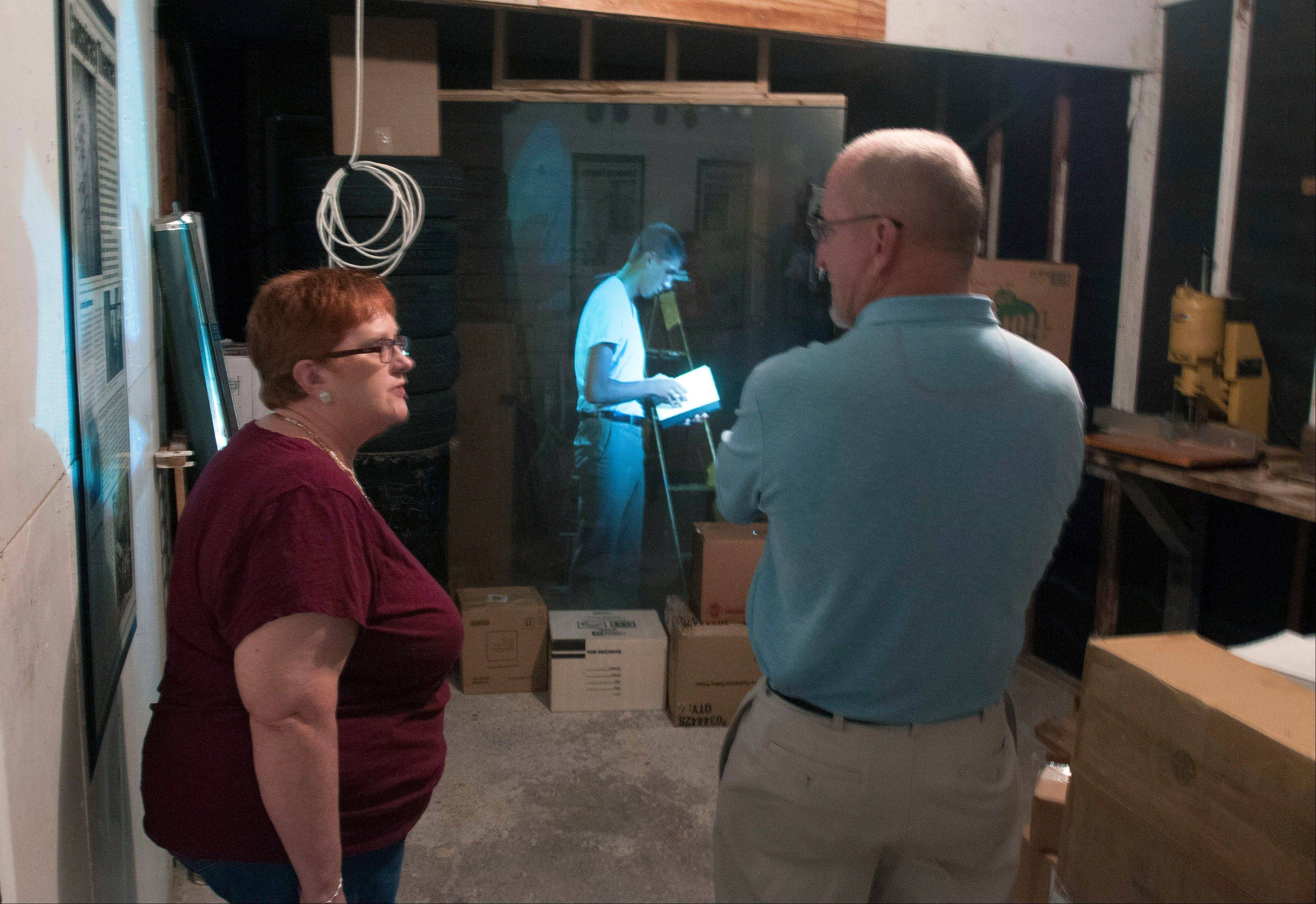 Shirley Smith, capital improvement program coordinator for the city of Irving, Texas, and building inspector Lawrence Crow talk in the garage at the Ruth Paine House Museum in Irving. The museum in the small, two-bedroom home that once belonged to Ruth Paine, who had befriended Lee Harvey Oswald's wife, Marina, and let her live there with her two daughters, opened Wednesday. In the background is a projection of an actor portraying Lee Harvey Oswald using a technique called Pepper's Ghost.