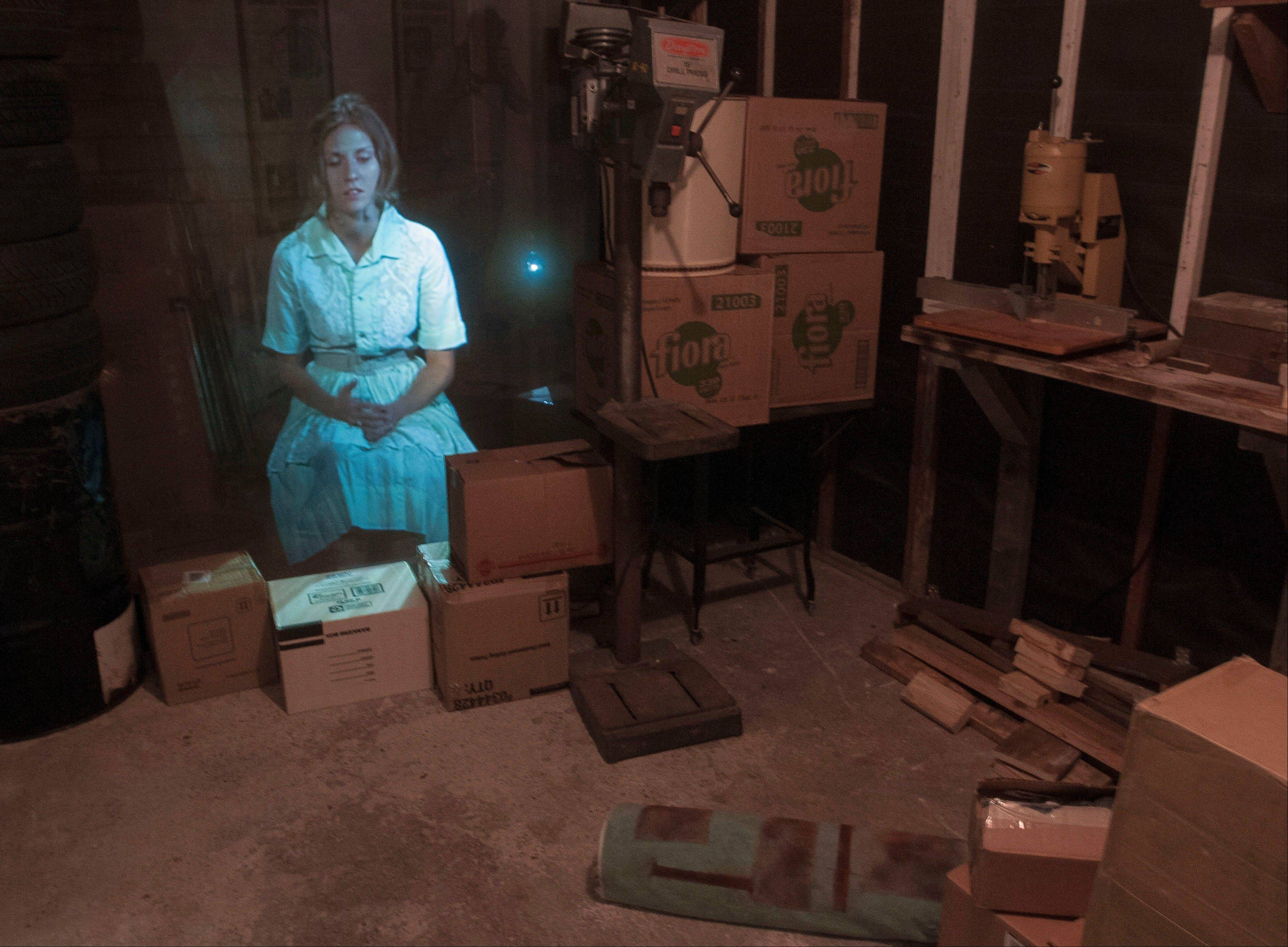 An image of an actress portraying Marina Oswald, wife of Lee Harvey Oswald, is projected in the garage of the Ruth Paine House Museum in Irving, Texas.