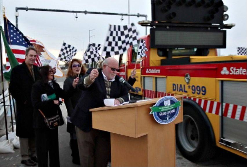 Huntley Mayor Charles Sass and other local and state dignitaries wave checkered flags as the first vehicles roll through the westbound entrance ramp to the Jane Addams Tollway Friday in Huntley.