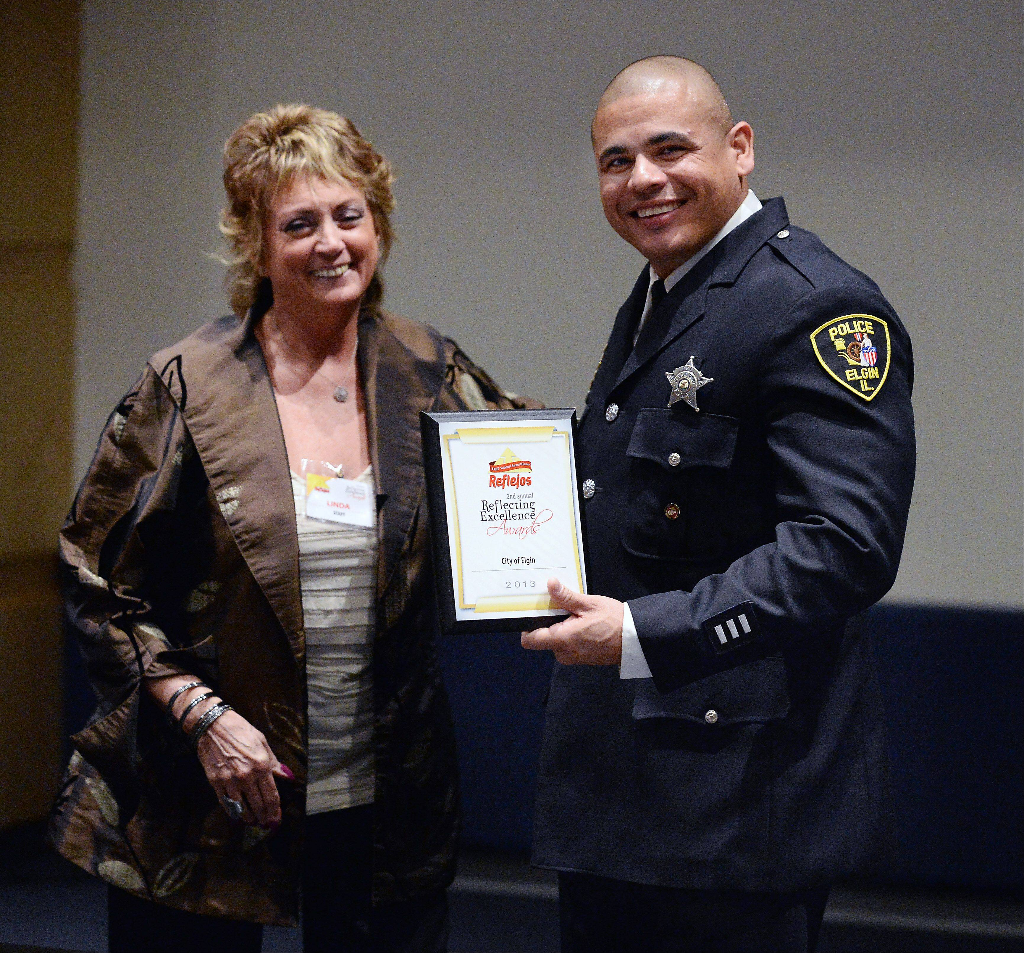 Linda Siete, sales operation manager at Reflejos, presents Officer Eric Echevarria of the Elgin Police Department with an award at the Daily Herald Reflejos Reflecting Excellence Awards event at Harper College on Thursday.