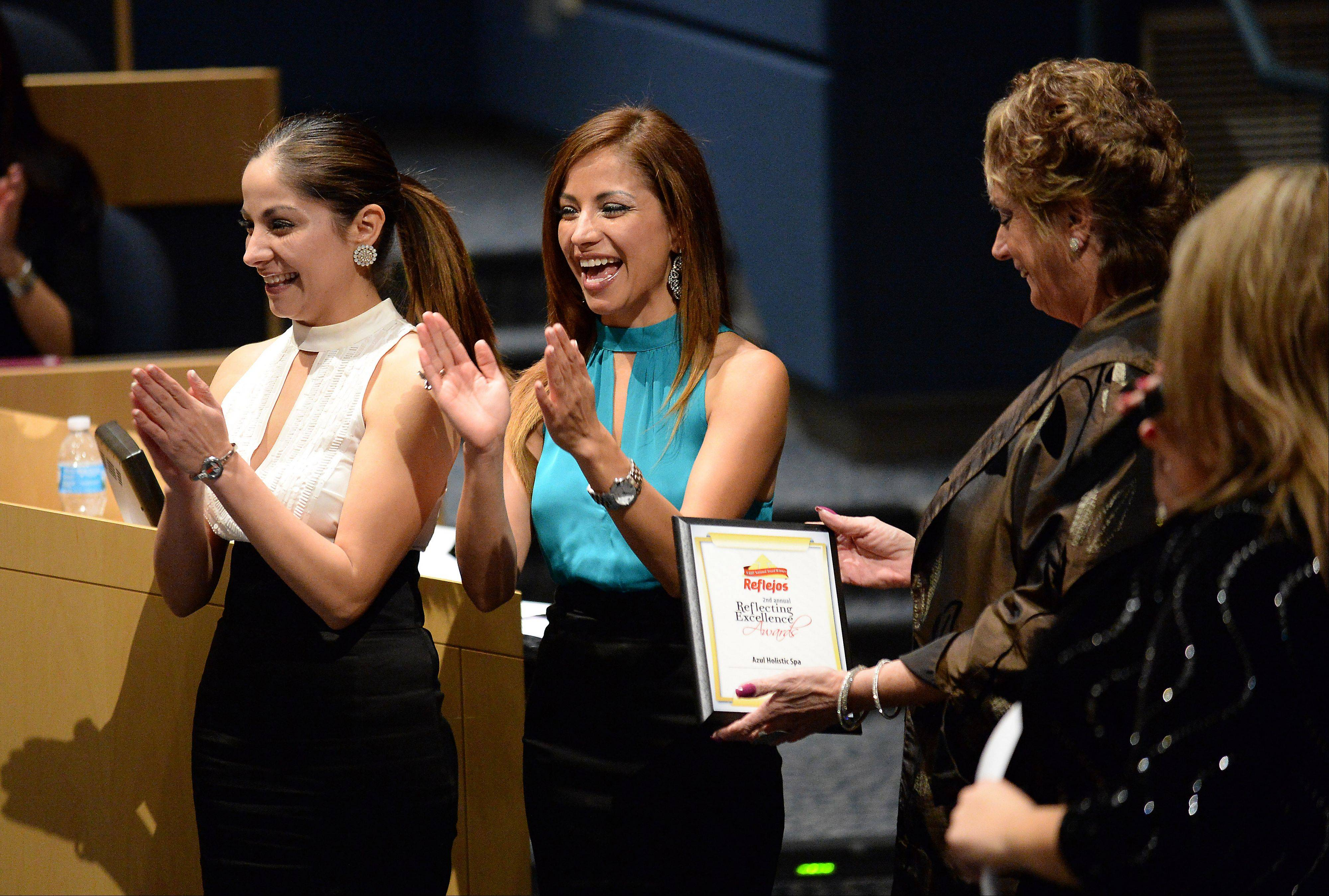 Linda Siete, sales operation manager at Reflejos, presents Silvia Romero, left, and Leticia Romero of the Azul Holistic Spa in Chicago with an award at the Daily Herald Reflejos Reflecting Excellence Awards event at Harper College on Thursday.