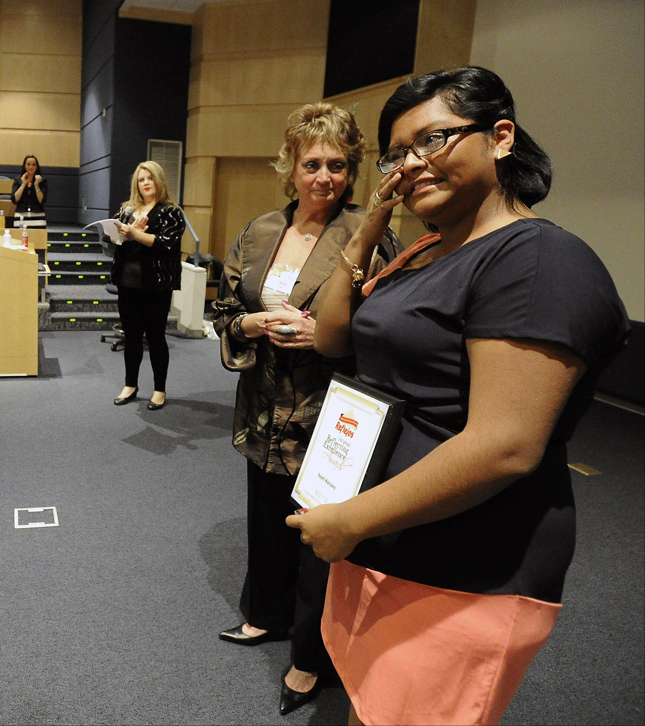 Linda Siete, sales operation manager at Reflejos, presents Nayeli Manzano from Bartlett High School with an award as she wipes away a tear at the Daily Herald Reflejos Reflecting Excellence Awards event at Harper College on Thursday.