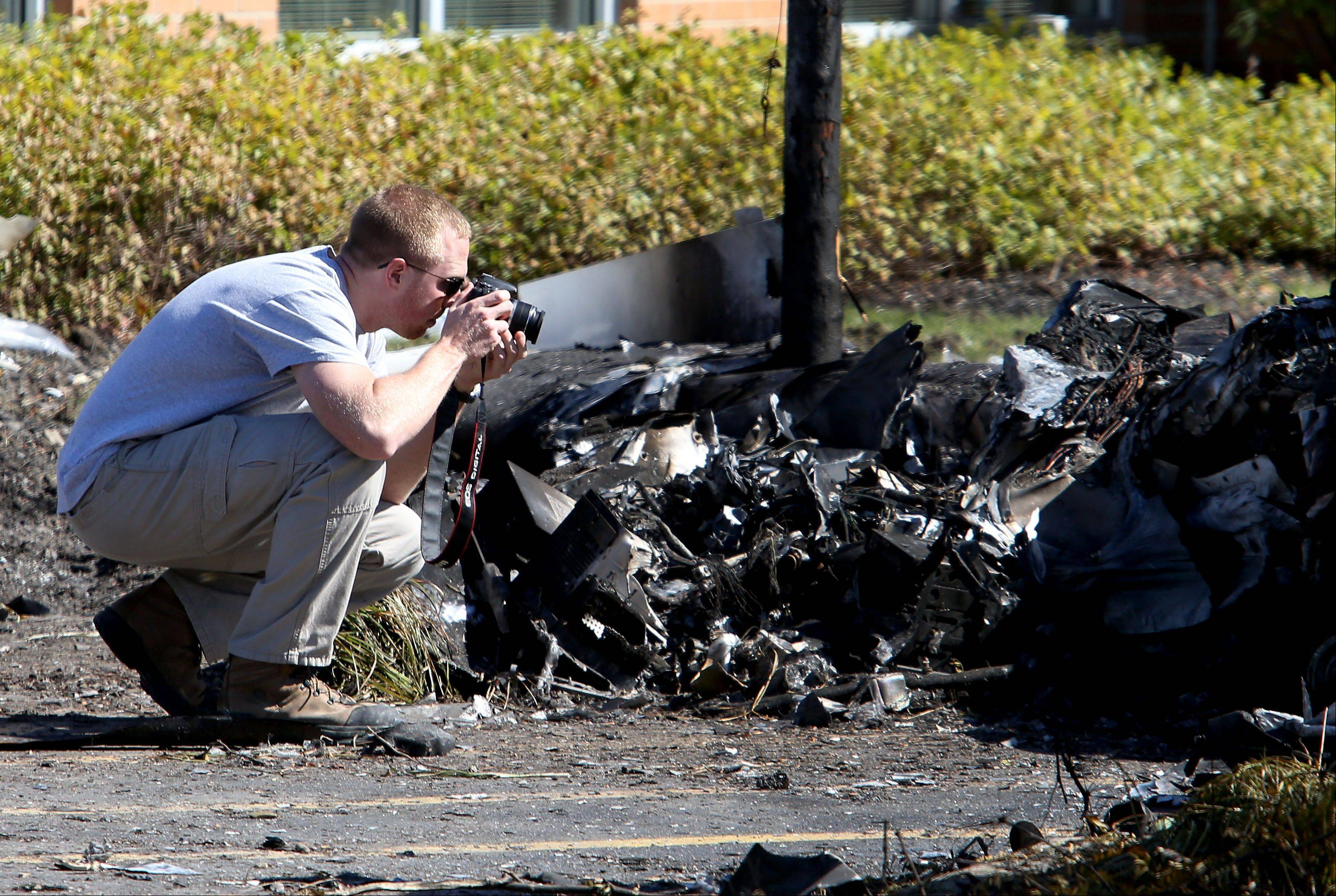 An investigator from the NTSB takes photographs of wreckage the day after a Sept. 25 plane crash in Bolingbrook.