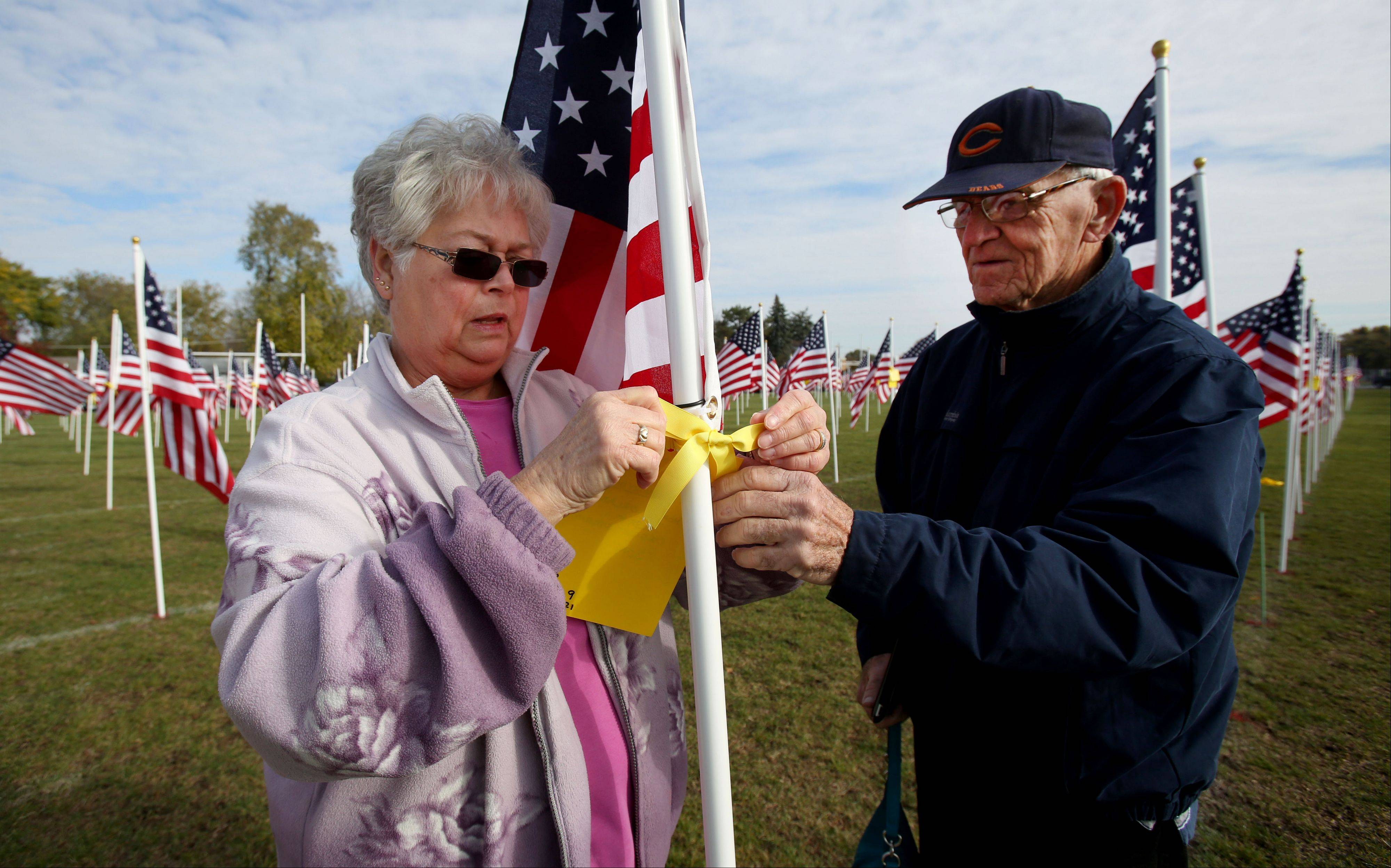 George and Jennifer Orland of Aurora attach a yellow tag in honor of son Tom Orland Thursday at the Healing Field of Honor at West Aurora High School.