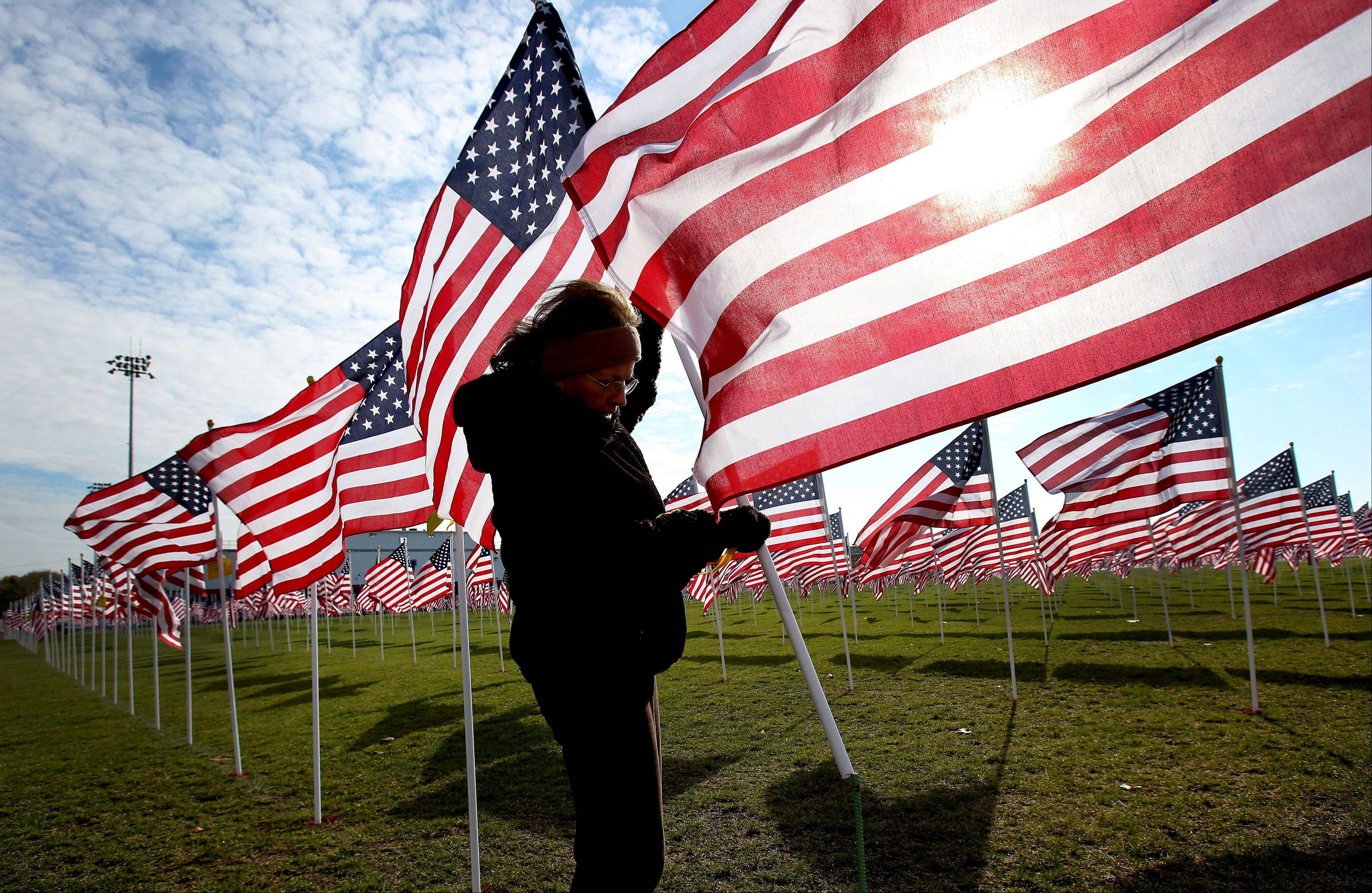 Sharon Catich of North Aurora puts a flag in its proper place Thursday at the Healing Field of Honor at West Aurora High School.