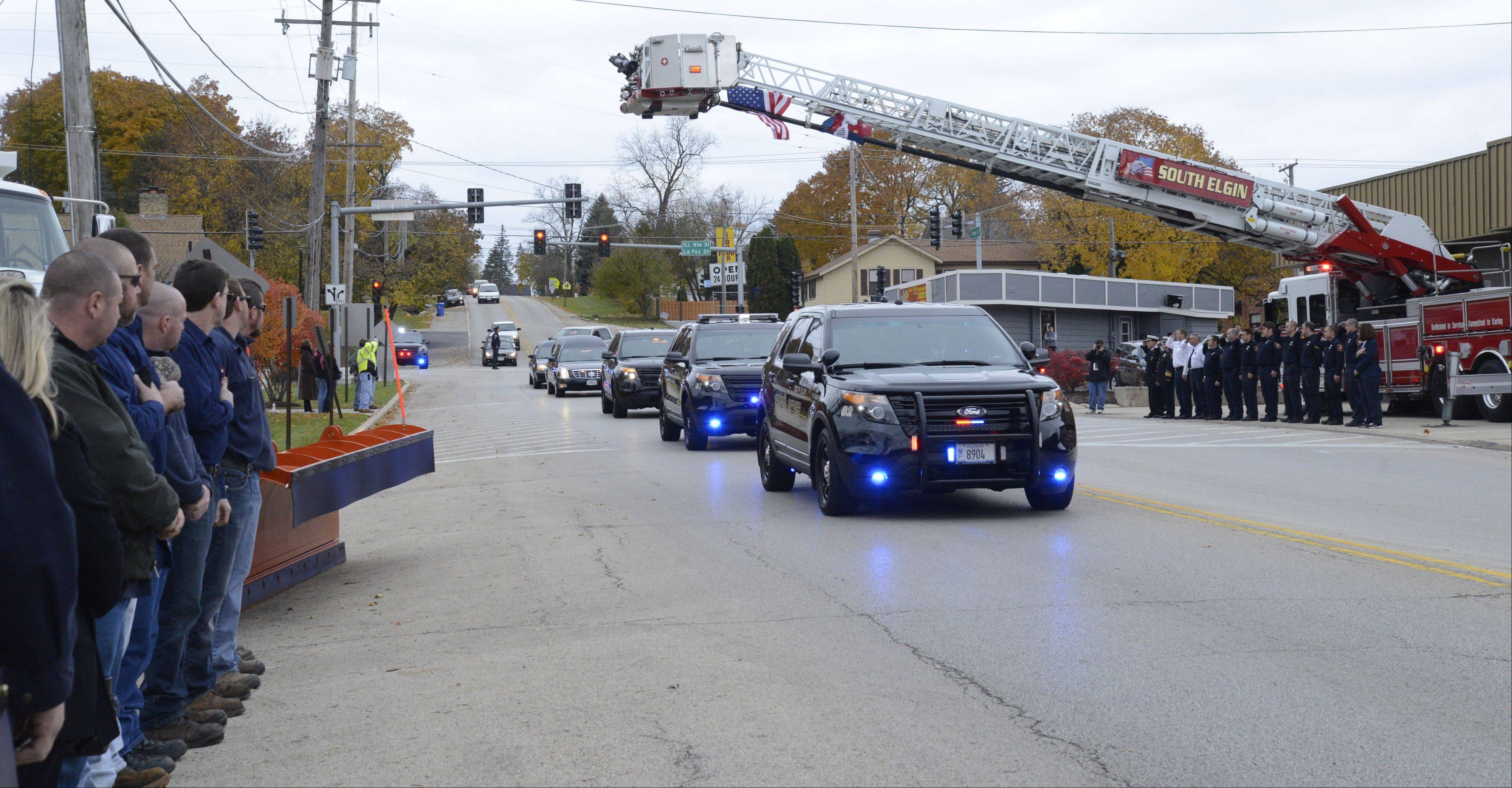 South Elgin police cars lead the funeral procession for Village President Jim Hansen past the town's fire department and village hall Thursday. Hansen died of lung cancer Nov. 1 at age 53.