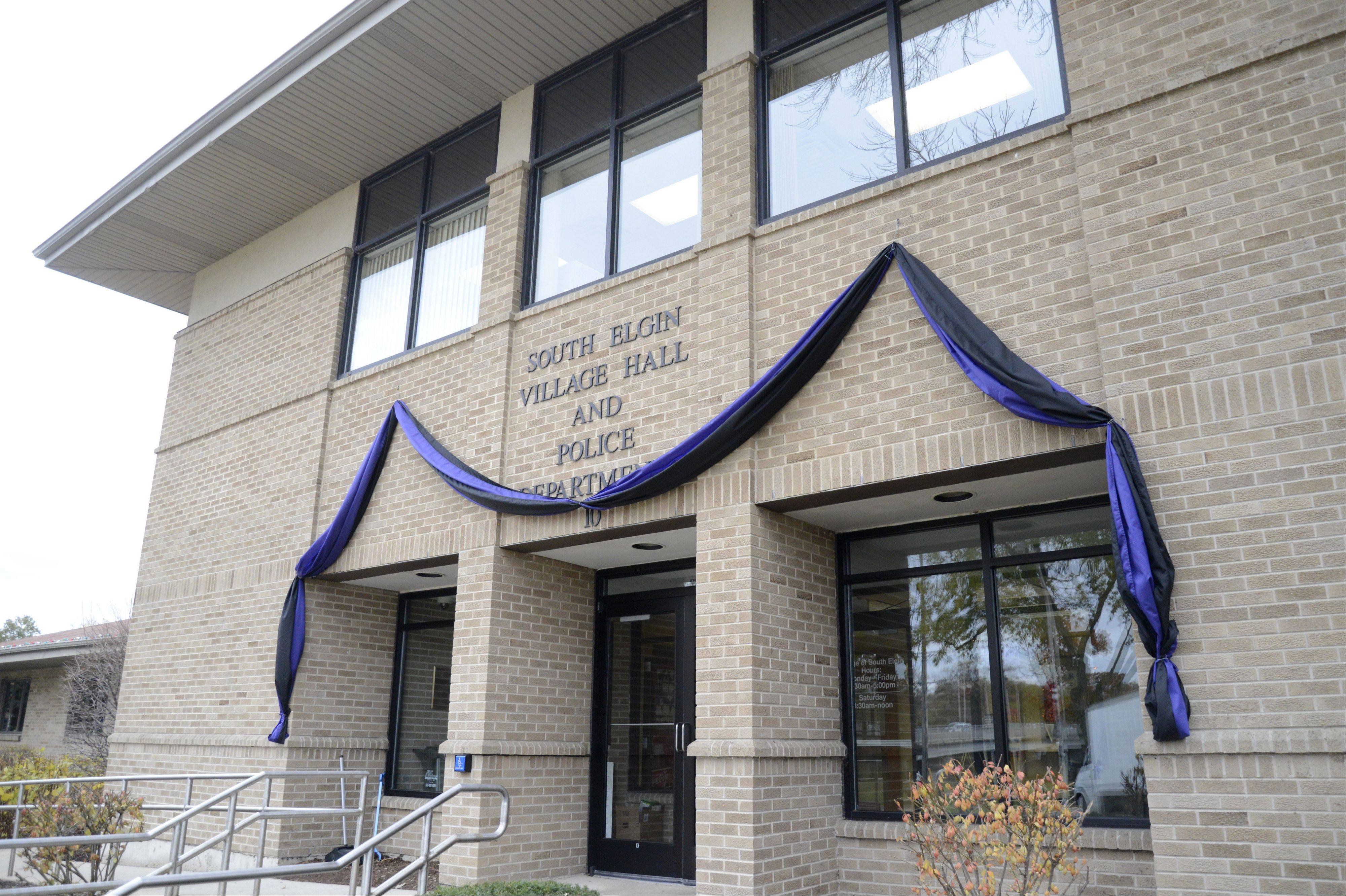 Black and purple bunting hangs from the entrance to the South Elgin's village hall and police department in honor of Village President Jim Hansen, who died Nov. 1.