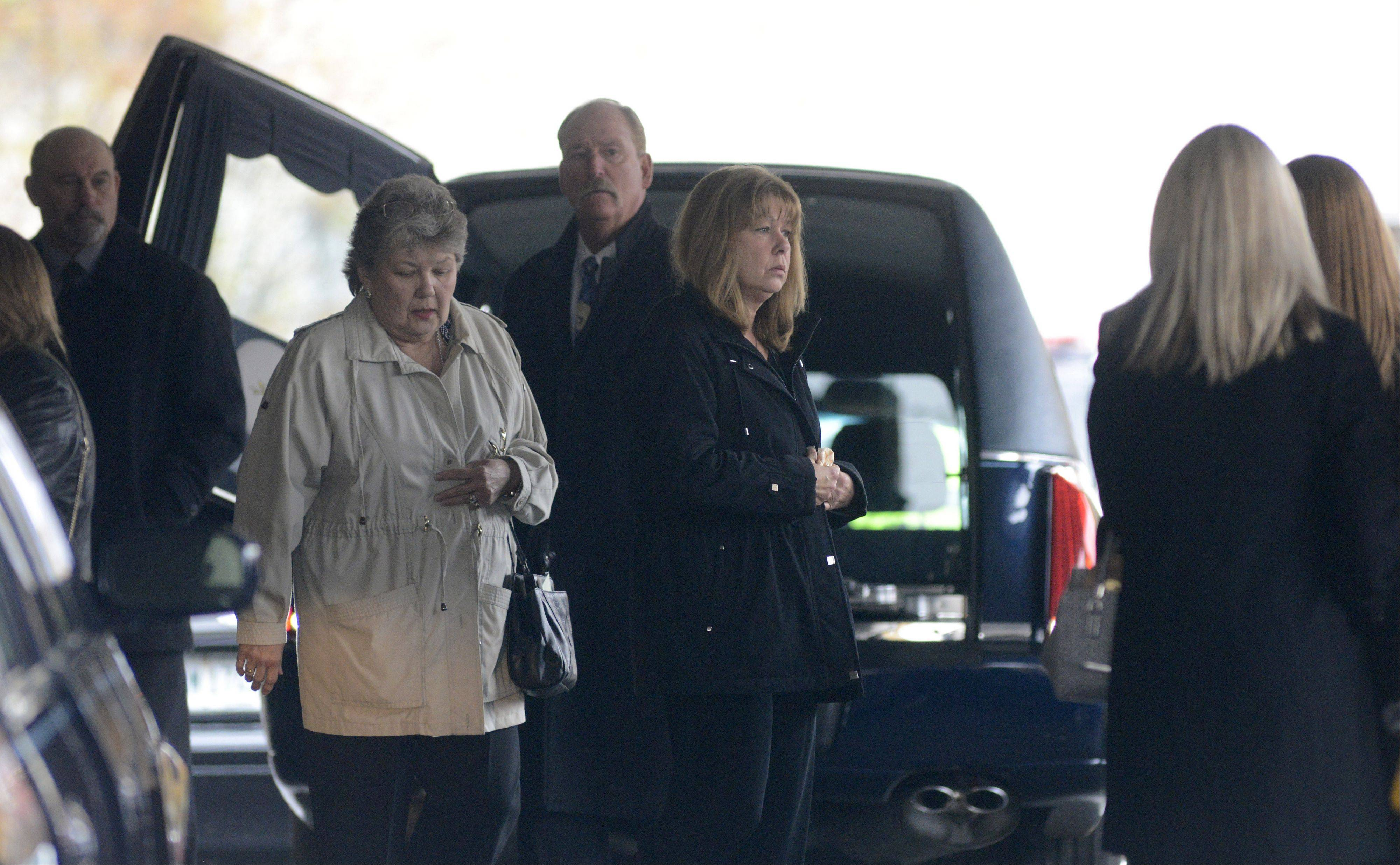 Teri Hansen (center, black jacket), widow of South Elgin Village President Jim Hansen, exits the Laird Funeral Home in Elgin Thursday with her mother, Bonnie Spencer.
