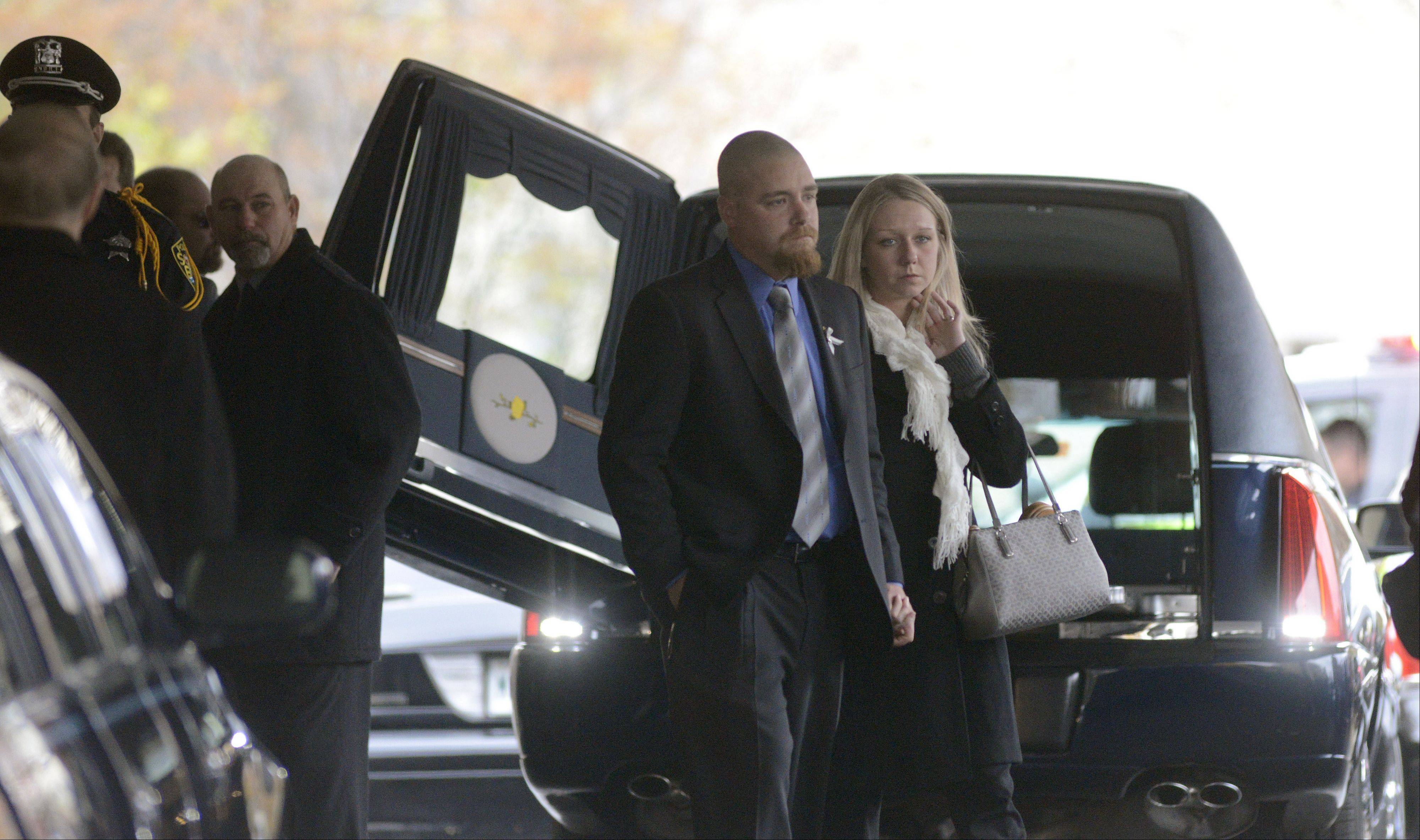 Dustin Hansen and his wife, Jennifer, depart Laird Funeral Home in Elgin Thursday after the funeral for his father, South Elgin Village President Jim Hansen.