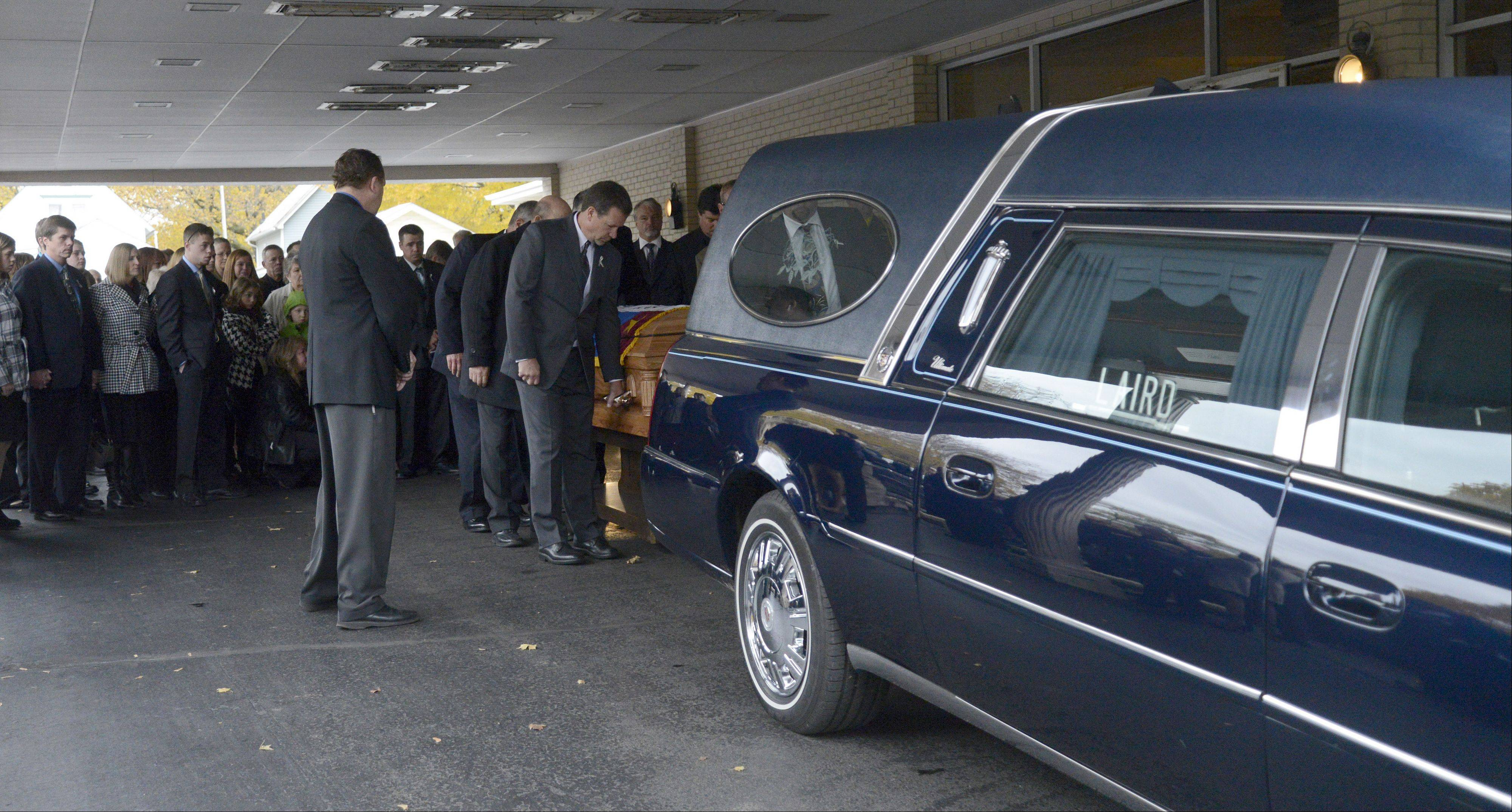 South Elgin Trustee Steve Ward, front, serves as a pallbearer at the funeral of Village President Jim Hansen Thursday.