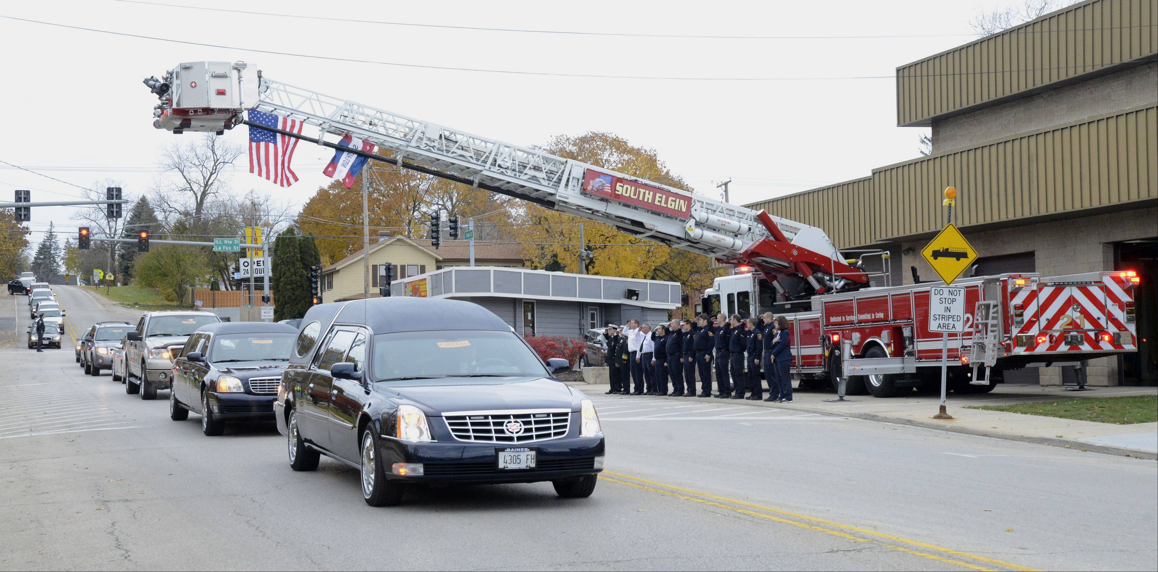 Members of the South Elgin Fire Department salute as the funeral procession for Village President Jim Hansen drives past the fire house and village hall Thursday.