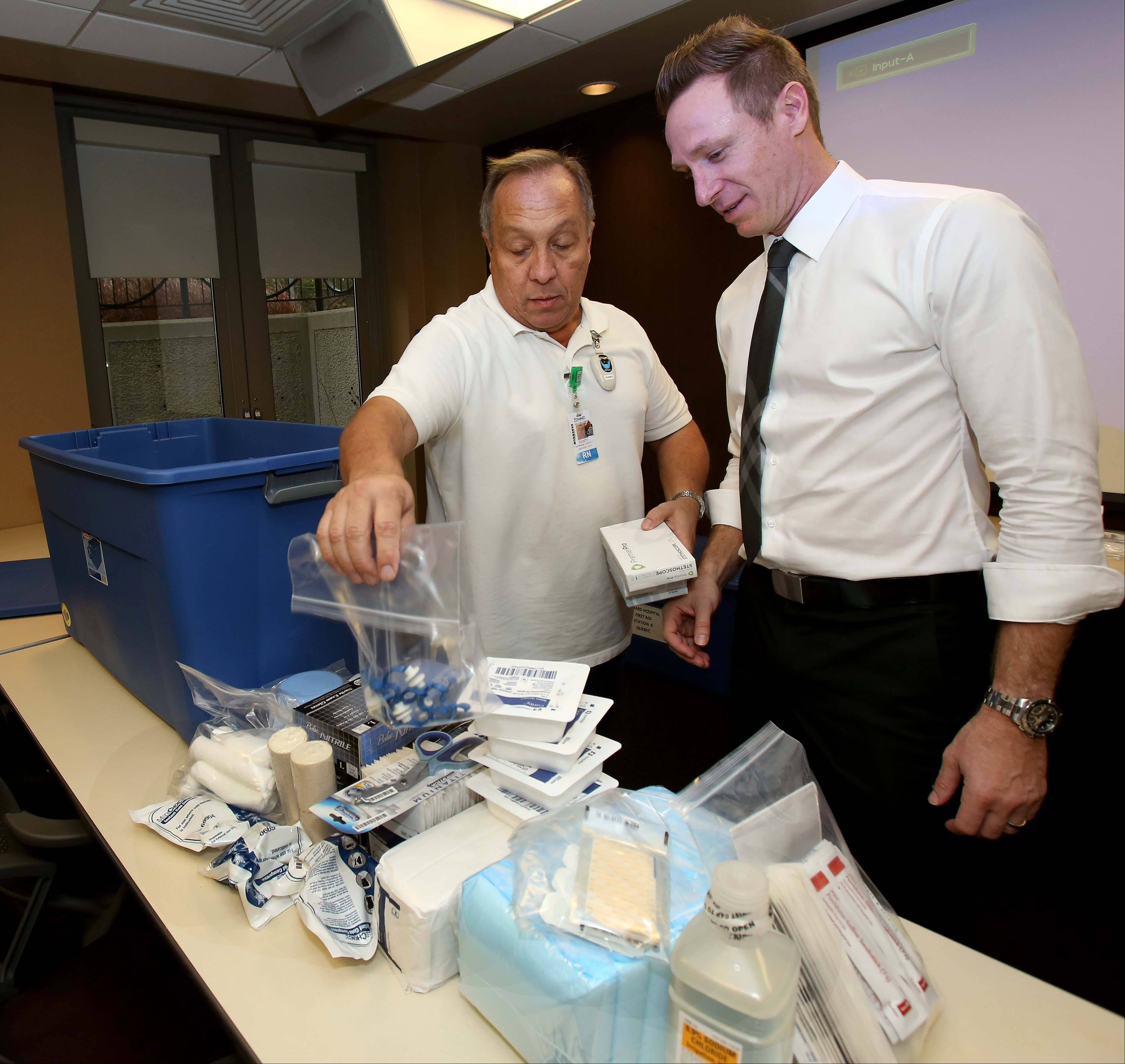Edward Hospital Emergency Room nurse Randy Schmidt and Dr. Michael Hartmann look over some of the supplies each aid station will receive Sunday for the inaugural Edward Hospital Naperville Marathon and Half Marathon.