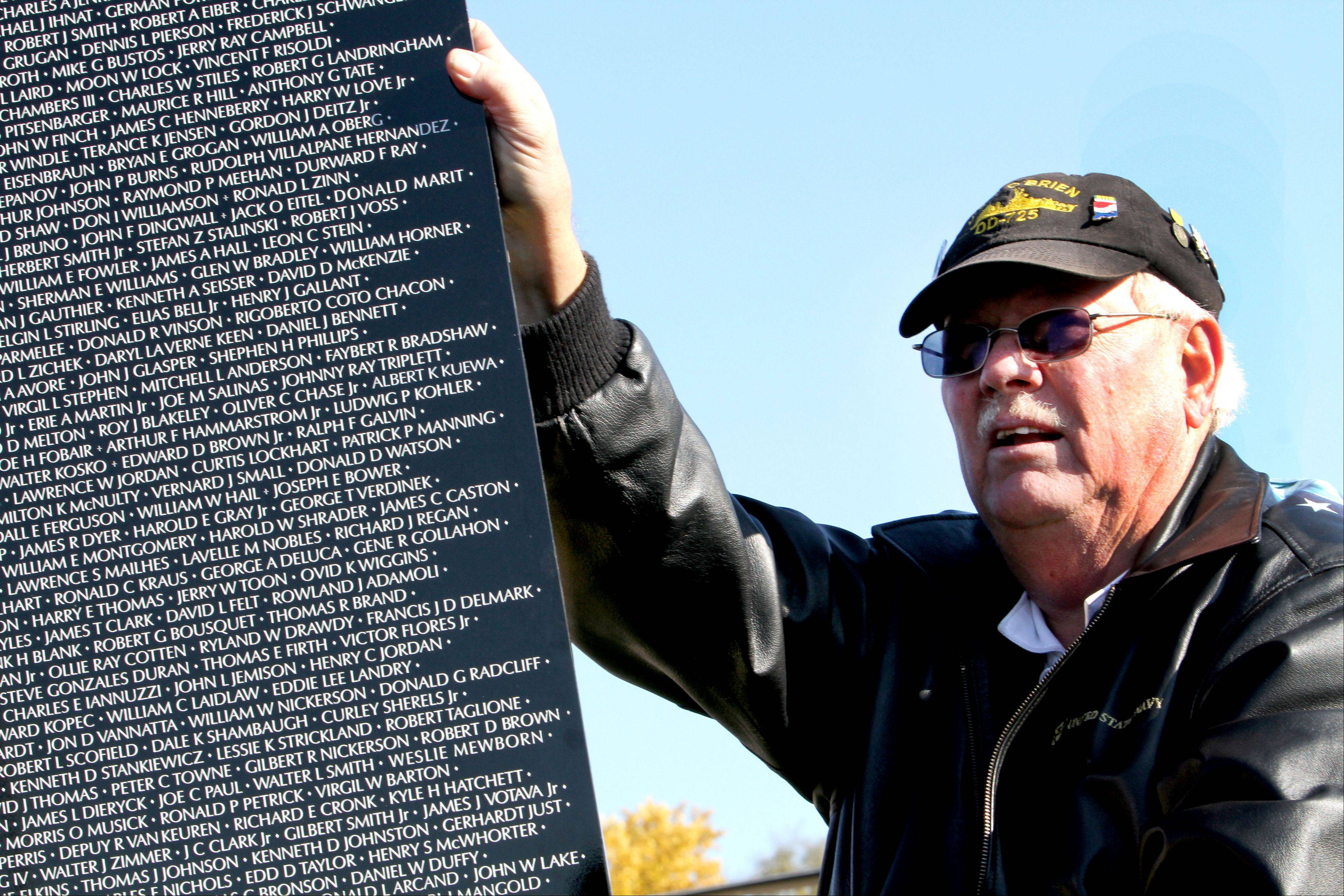 Herschel Luckinbill, chairman of the Vietnam Moving Wall in Aurora, holds a piece of the wall as it's set up on the West Aurora High School campus.