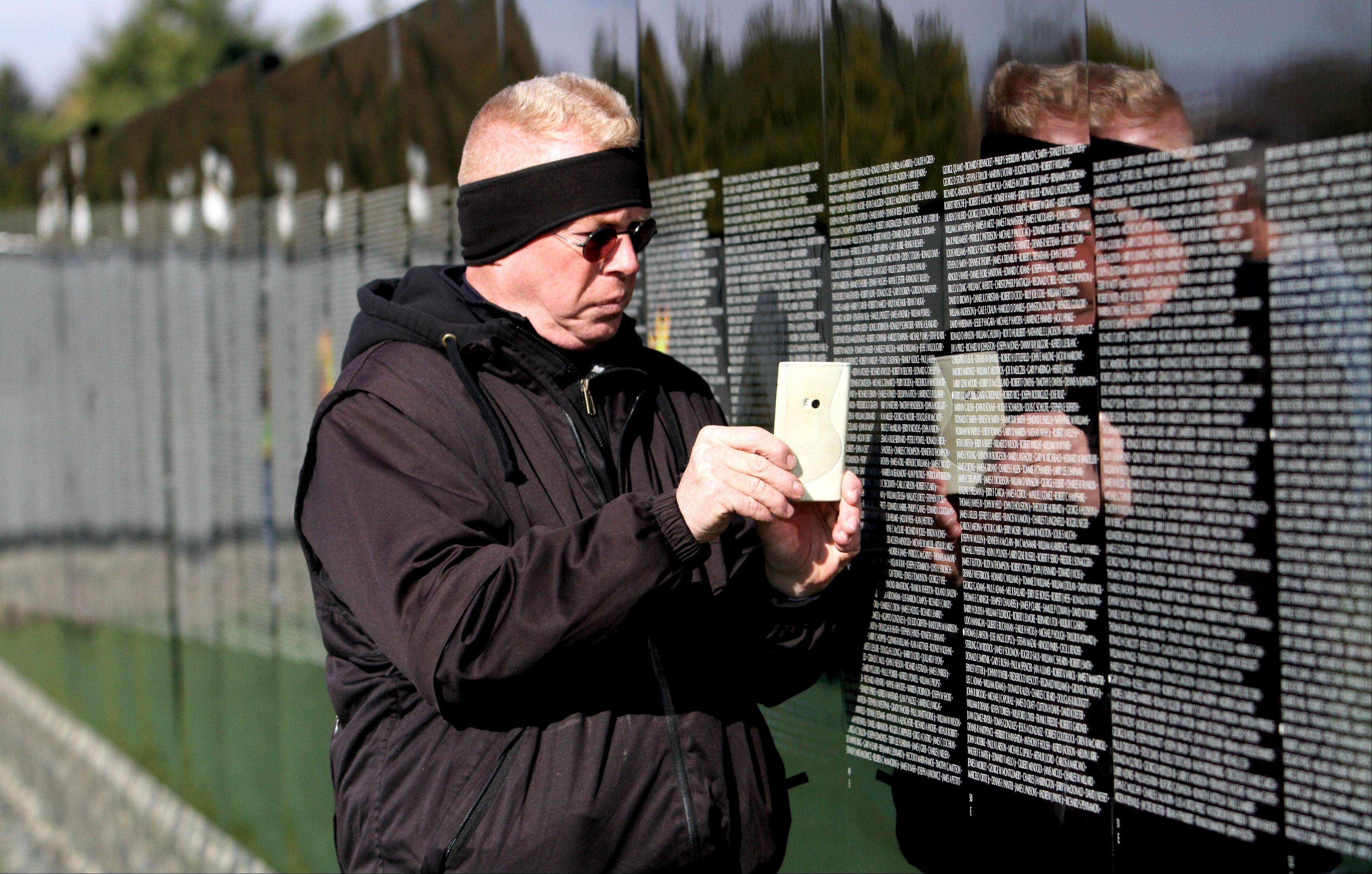 Jerald Willoughby of St. Charles finds the name of his brother, Jesse Willoughby, on The Moving Wall at the West Aurora High School campus.