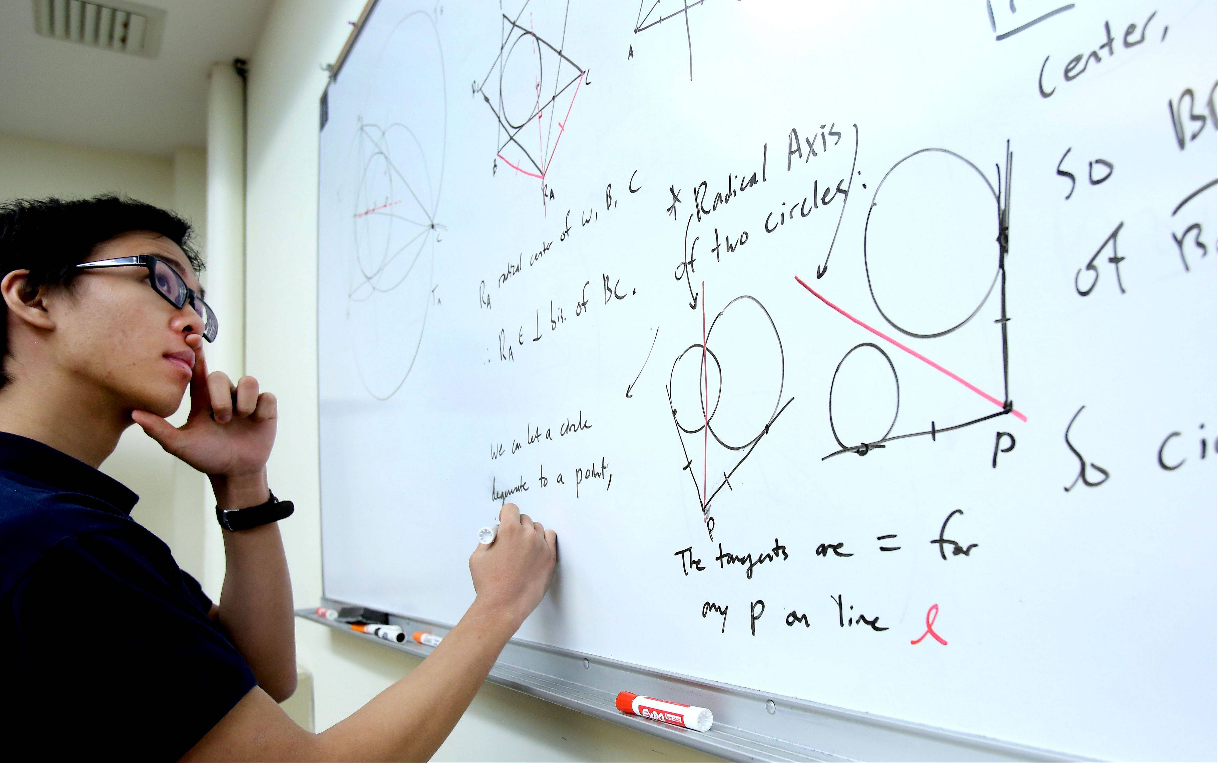 James Tao, a senior at the Illinois Mathematics and Science Academy in Aurora, solves a math problem from the Romanian Mathematical Olympiad in 2012. He didn't solve it at the contest, but solved it on the plane coming home.
