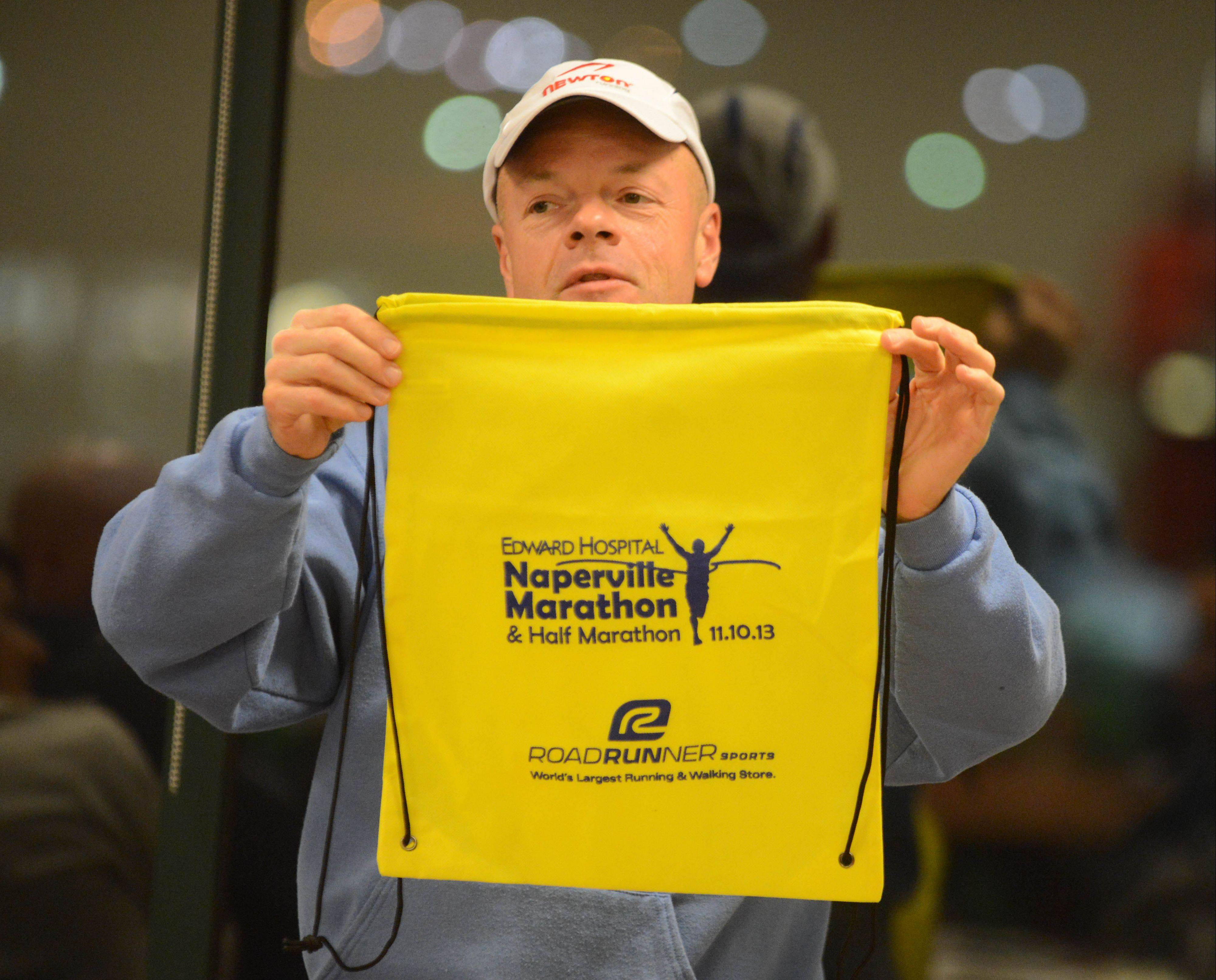 Tom Horvath displays the gear bag each registered runner will receive during an October meeting of volunteers for the Edward Hospital Marathon and Half Marathon.