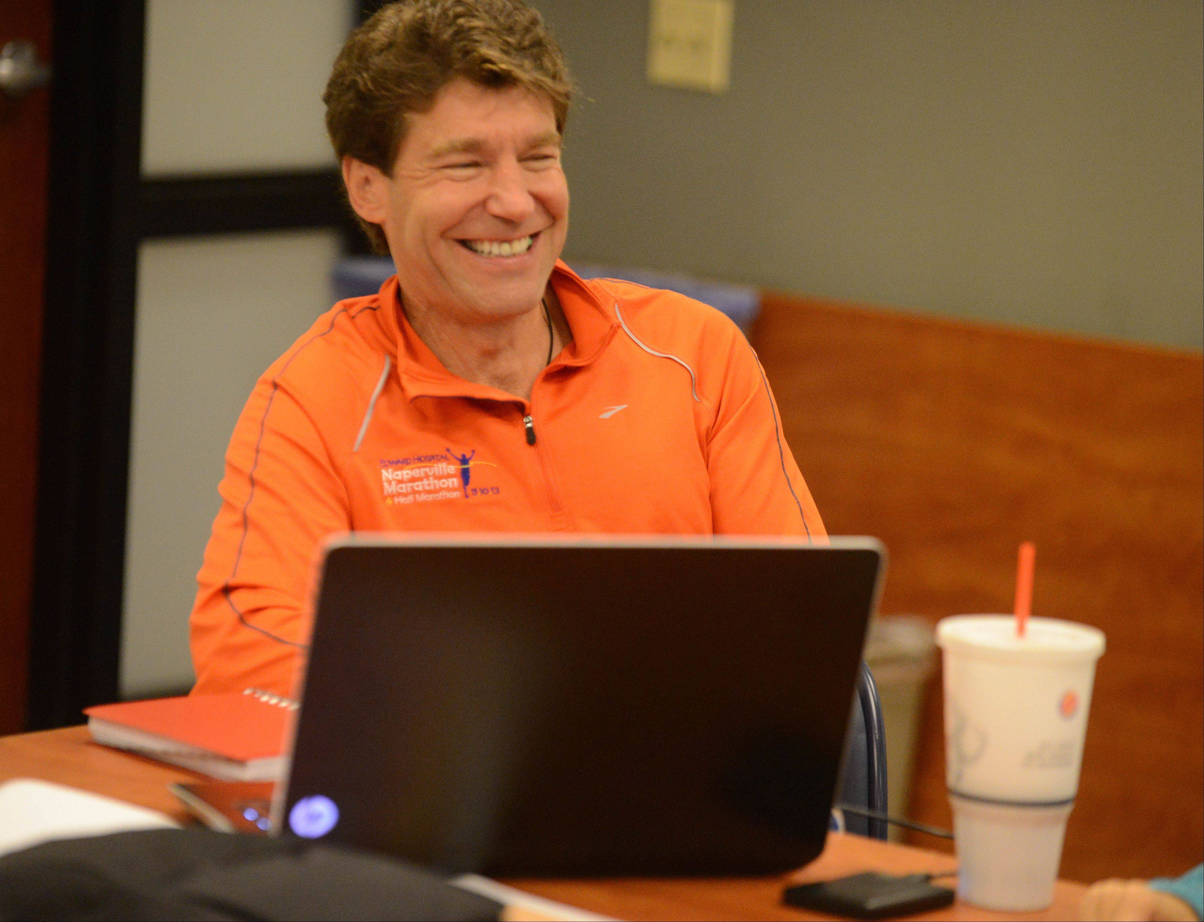 Craig Bixler, one of five directors of the Edward Hospital Naperville Marathon and Half Marathon, laughs along with volunteers who will help make the race possible during a planning meeting in October.