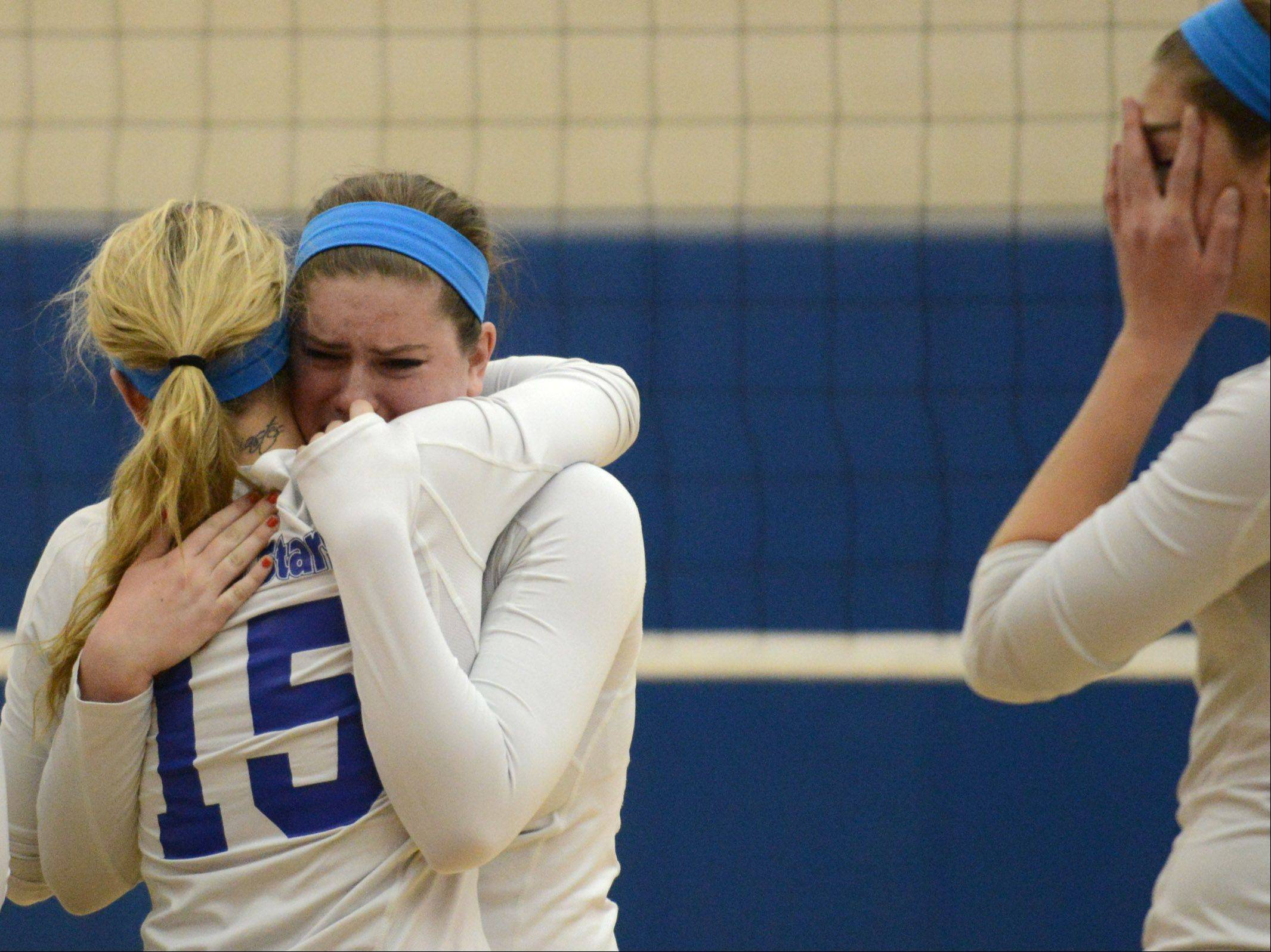 St. Charles North's Corrinne Sullivan, facing, hugs teammate Camille Kot after their loss to Geneva during Thursday's sectional final in Geneva.