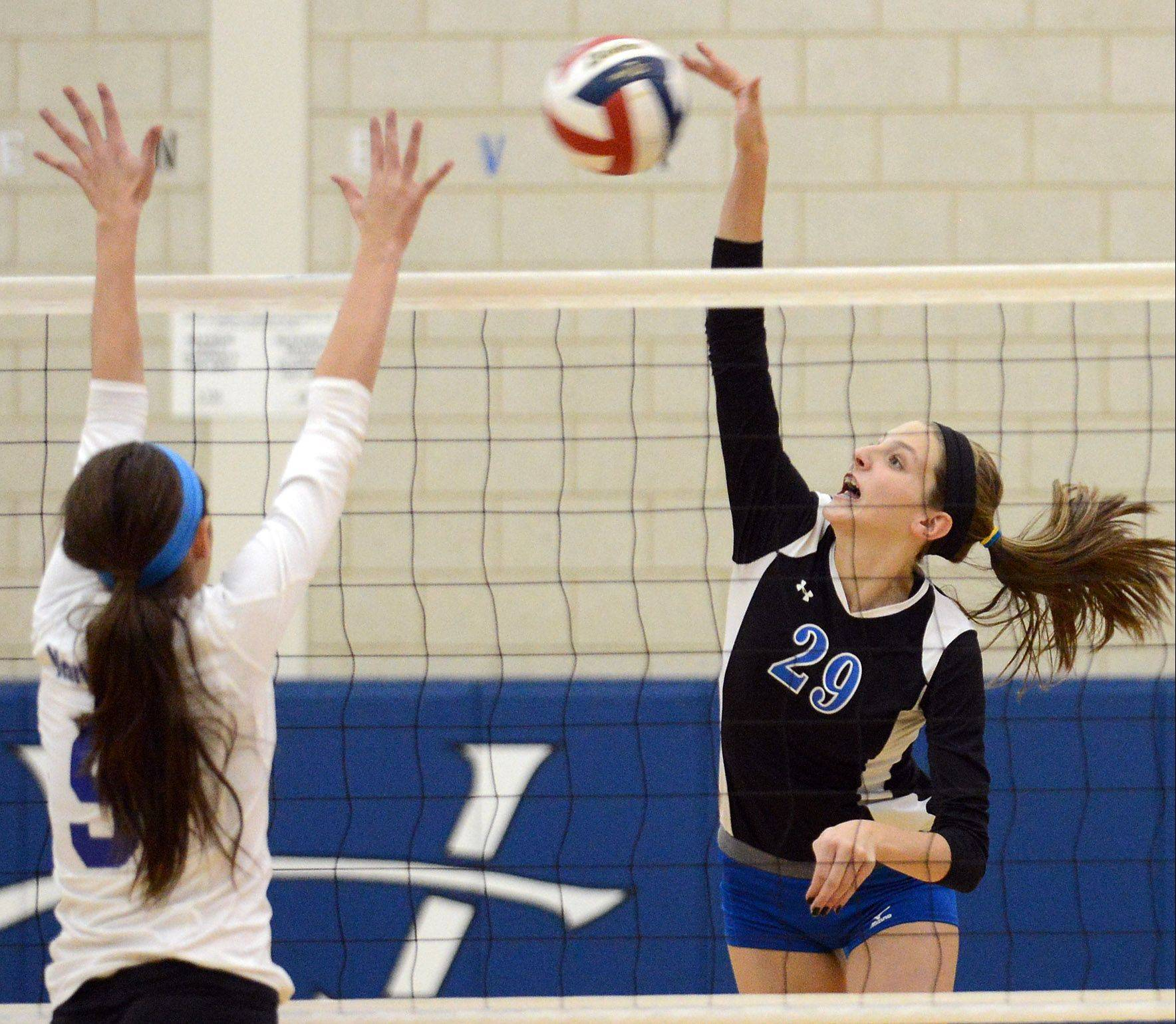 Geneva's Grace Loberg hits over St. Charles North's Jaclyn Taylor.