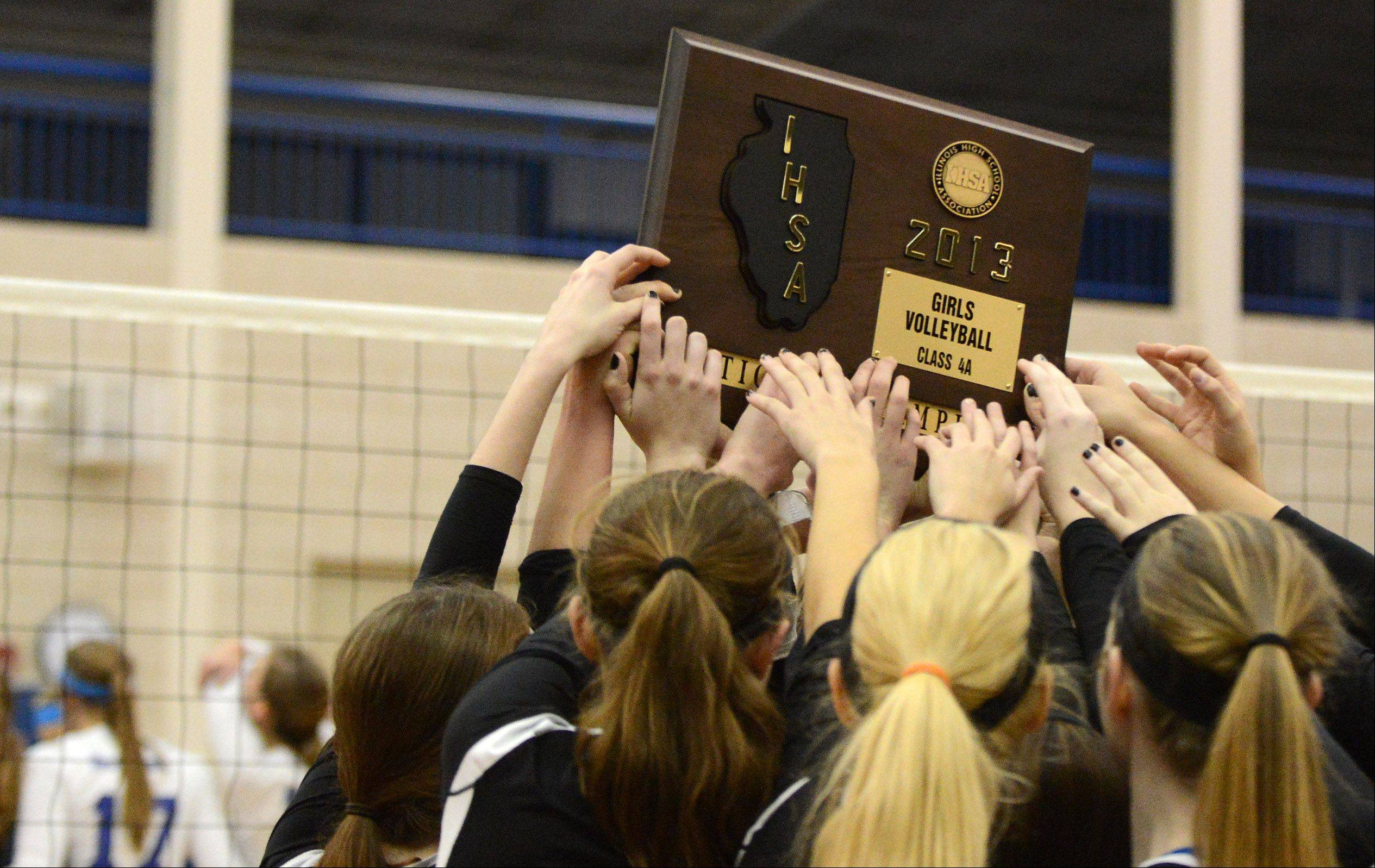 Geneva players all reach for a piece of the sectional trophy following their win over St. Charles North during Thursday's sectional final in Geneva.