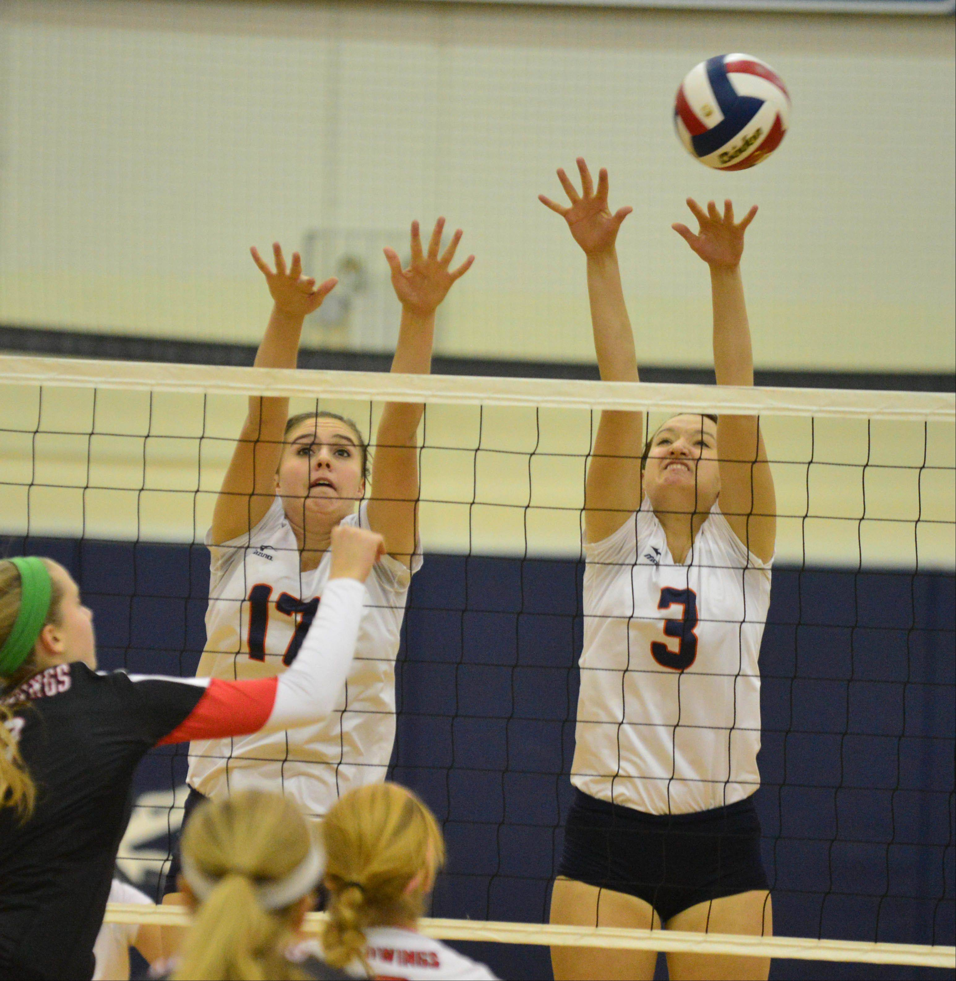 Maddi Henry,left, and Angela Jurek of Naperville North go up for a block during the Benet vs. Naperville North Class 4A Plainfield South girls volleyball sectional final Thursday.