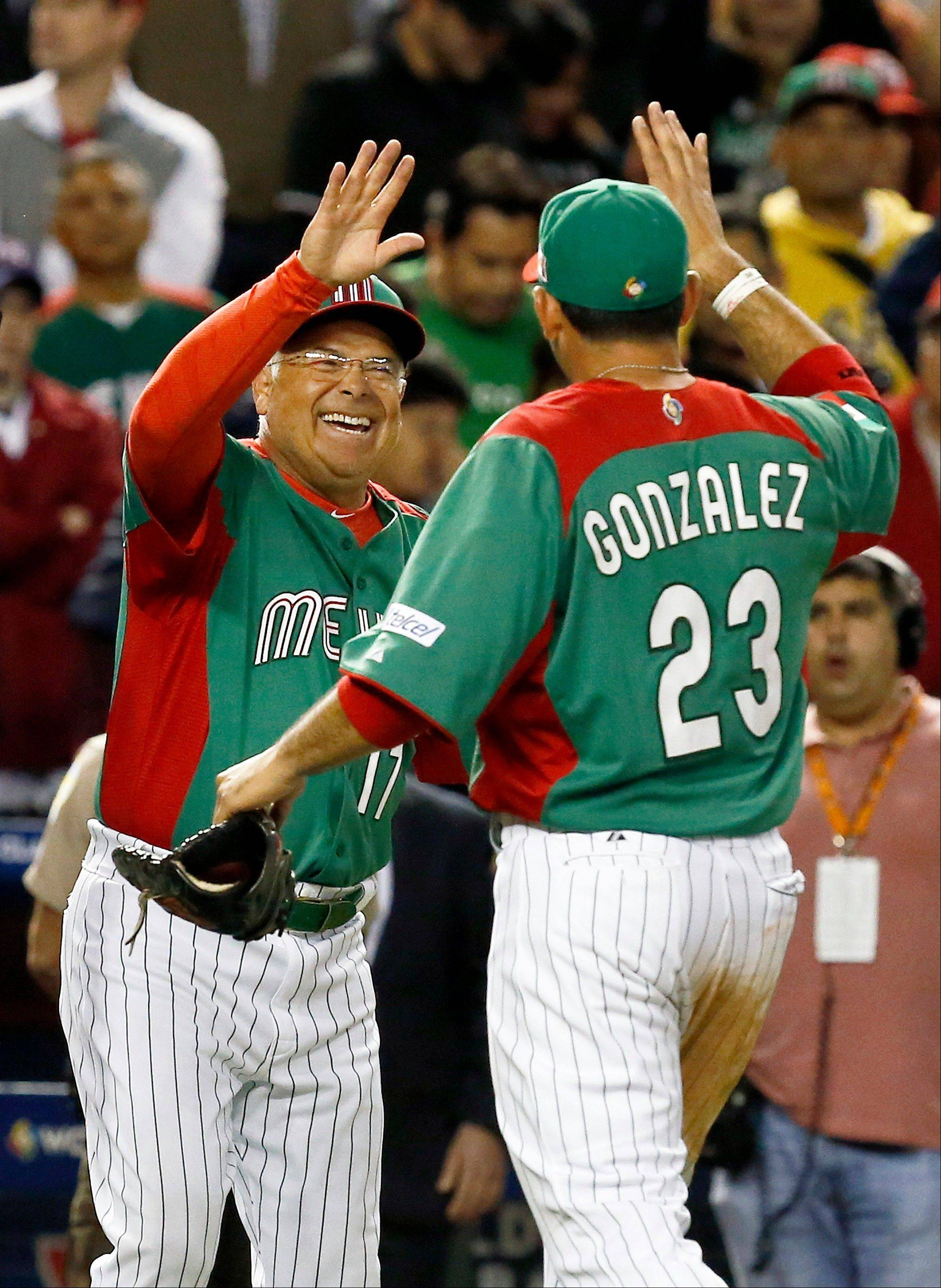 Rick Renteria, left, smiles as he celebrates a win by Team Mexico over the United States with Adrian Gonzalez (23) in the World Baseball Classic. Renteria is now the manager of the Cubs and expects his team to compete right away.