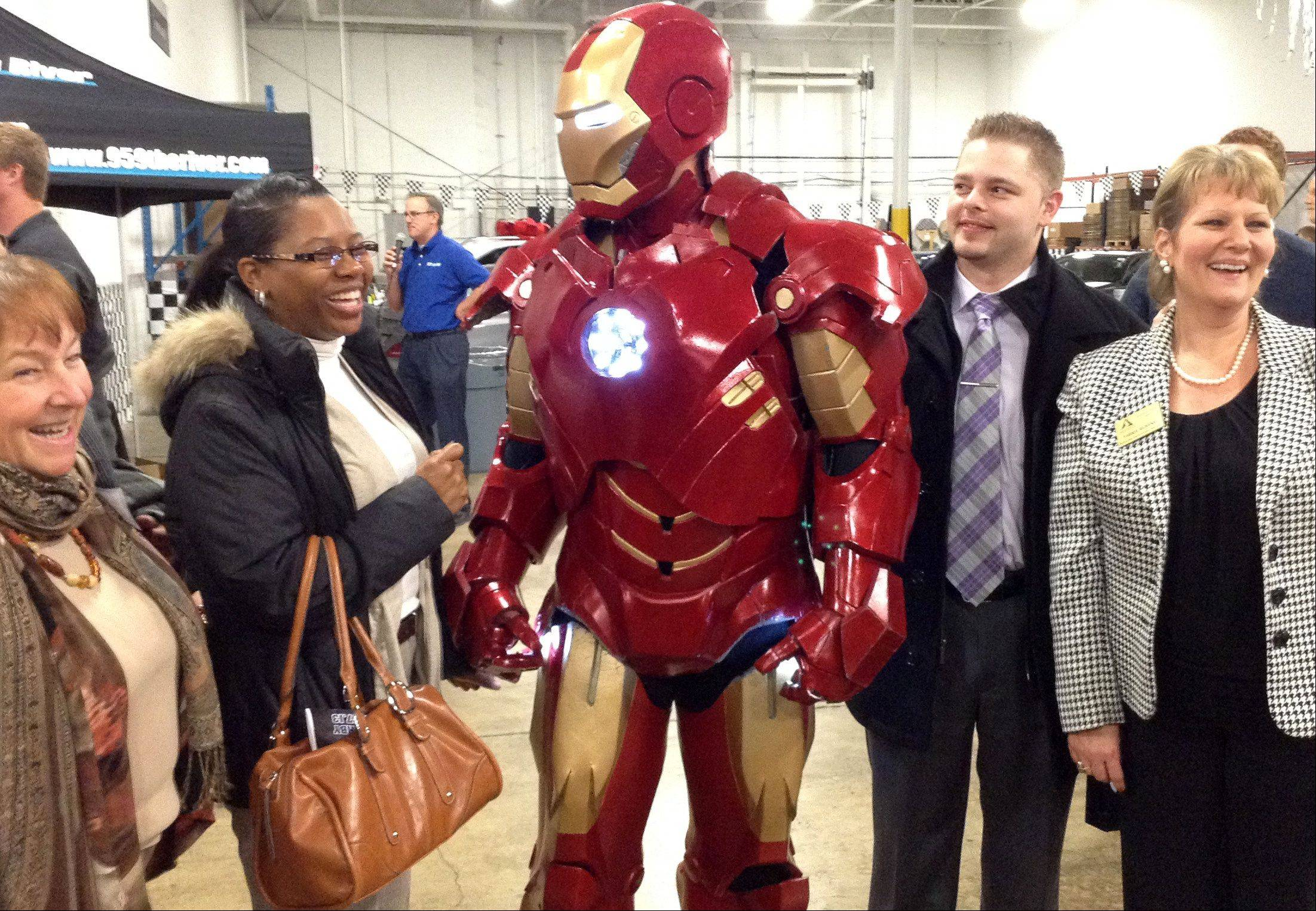 Iron Man has some fun with attendees of the Schaumburg Business Association's first Grand Prix Auto Derby Thursday night at MTA Advanced Automotive Solutions in Schaumburg