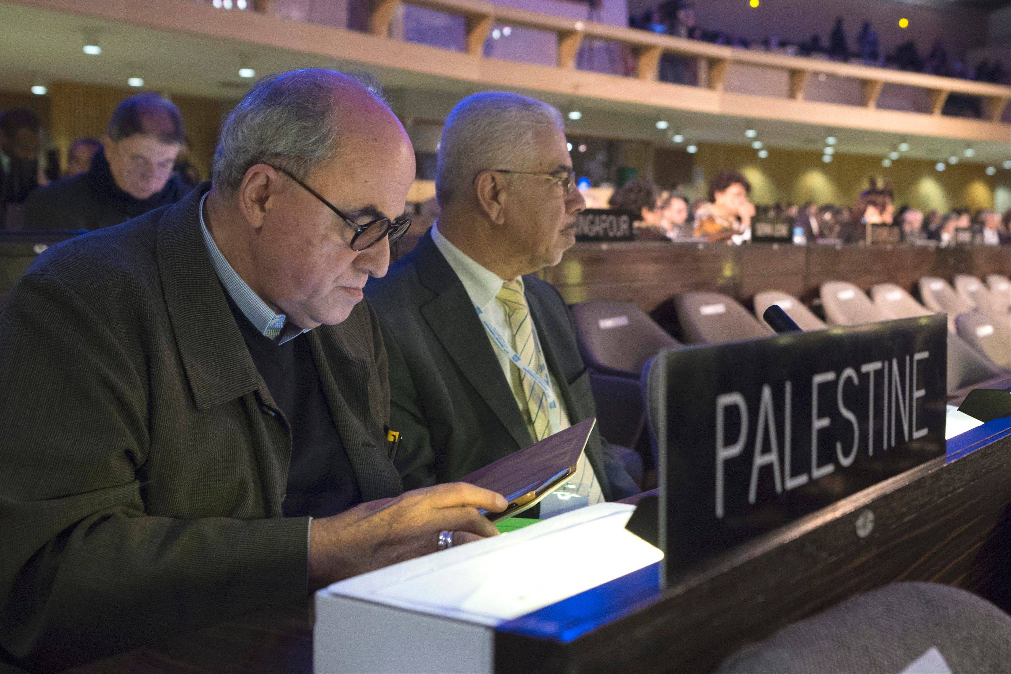 The Palestinian Ambassador to UNESCO Elias Sanbar, left, checks his tablet Friday during a session of the UNESCO General Conference in Paris. American influence in culture, science and education around the world took a high-profile blow Friday after the U.S. automatically lost voting rights at UNESCO, after missing a crucial deadline to repay its debt to the world�s cultural agency.