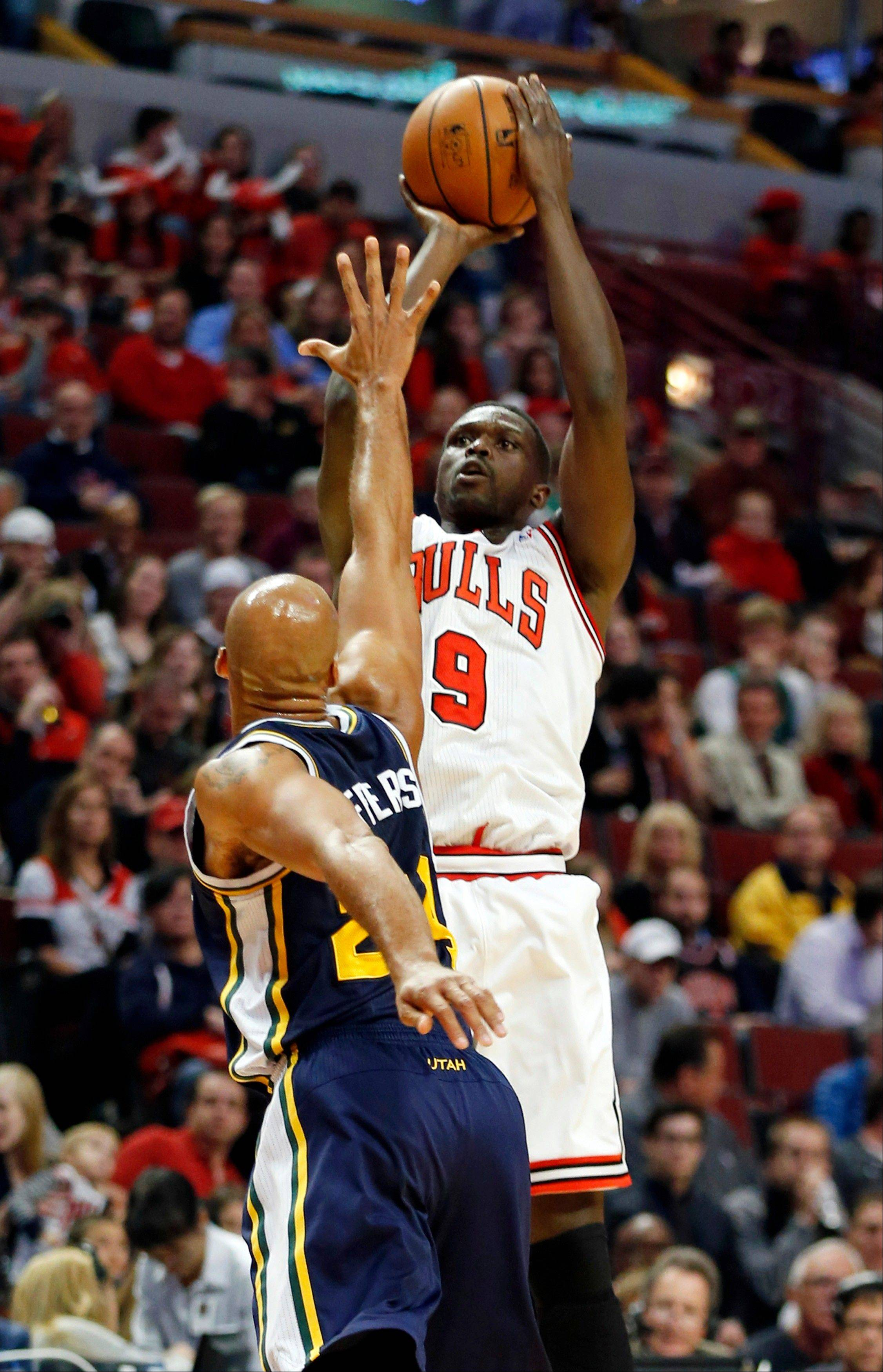 Chicago Bulls forward Luol Deng (9) shoots over Utah Jazz forward Richard Jefferson during the first quarter of an NBA basketball game in Chicago, Friday, Nov. 8, 2013. (AP Photo/Kamil Krzaczynski)