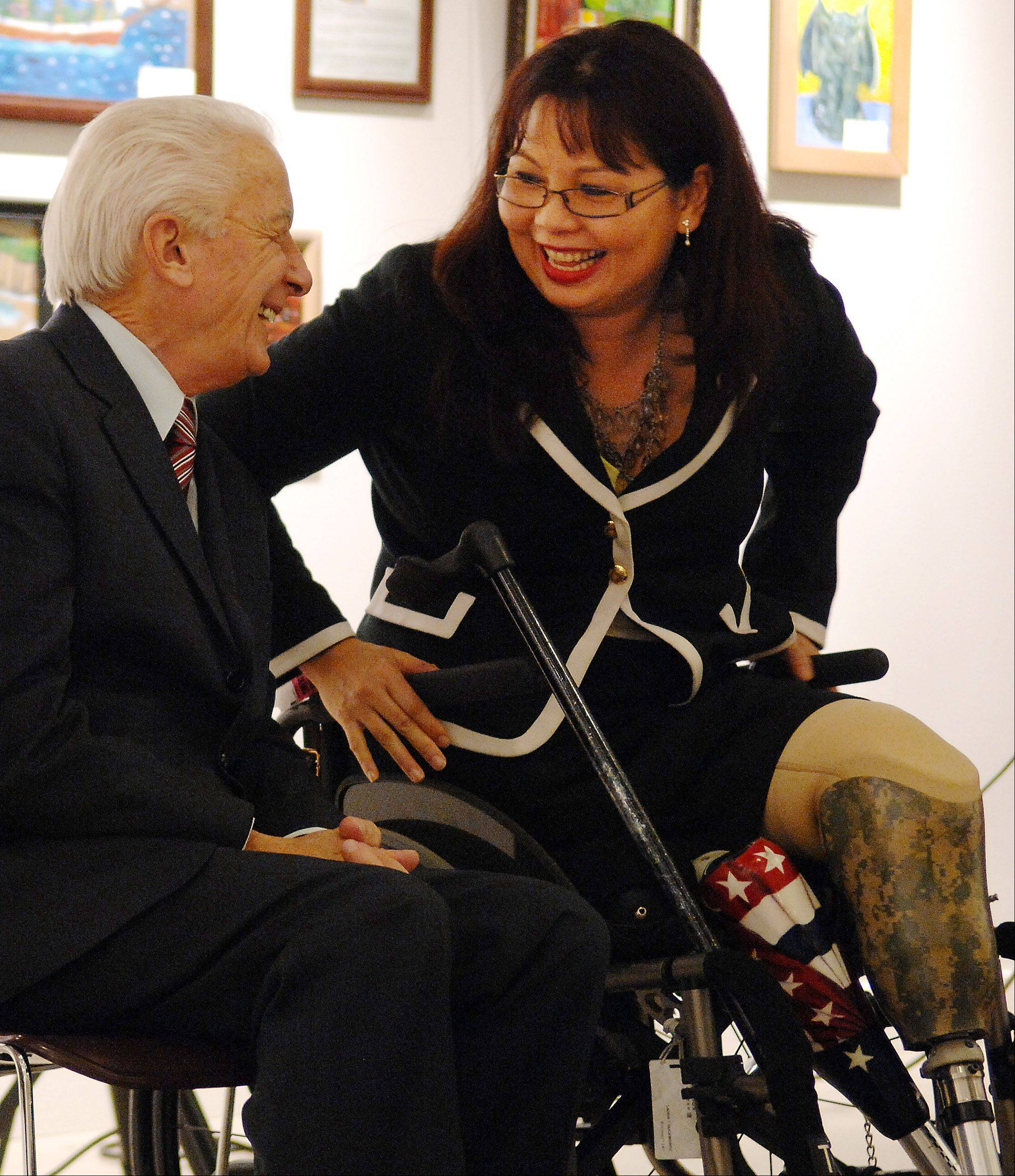 "U.S. Rep. Tammy Duckworth chats with state Rep. Keith Farnham after speaking at the opening of ""Salute to Women Veterans: Past and Present"" on Friday at Elgin ArtSpace Lofts."