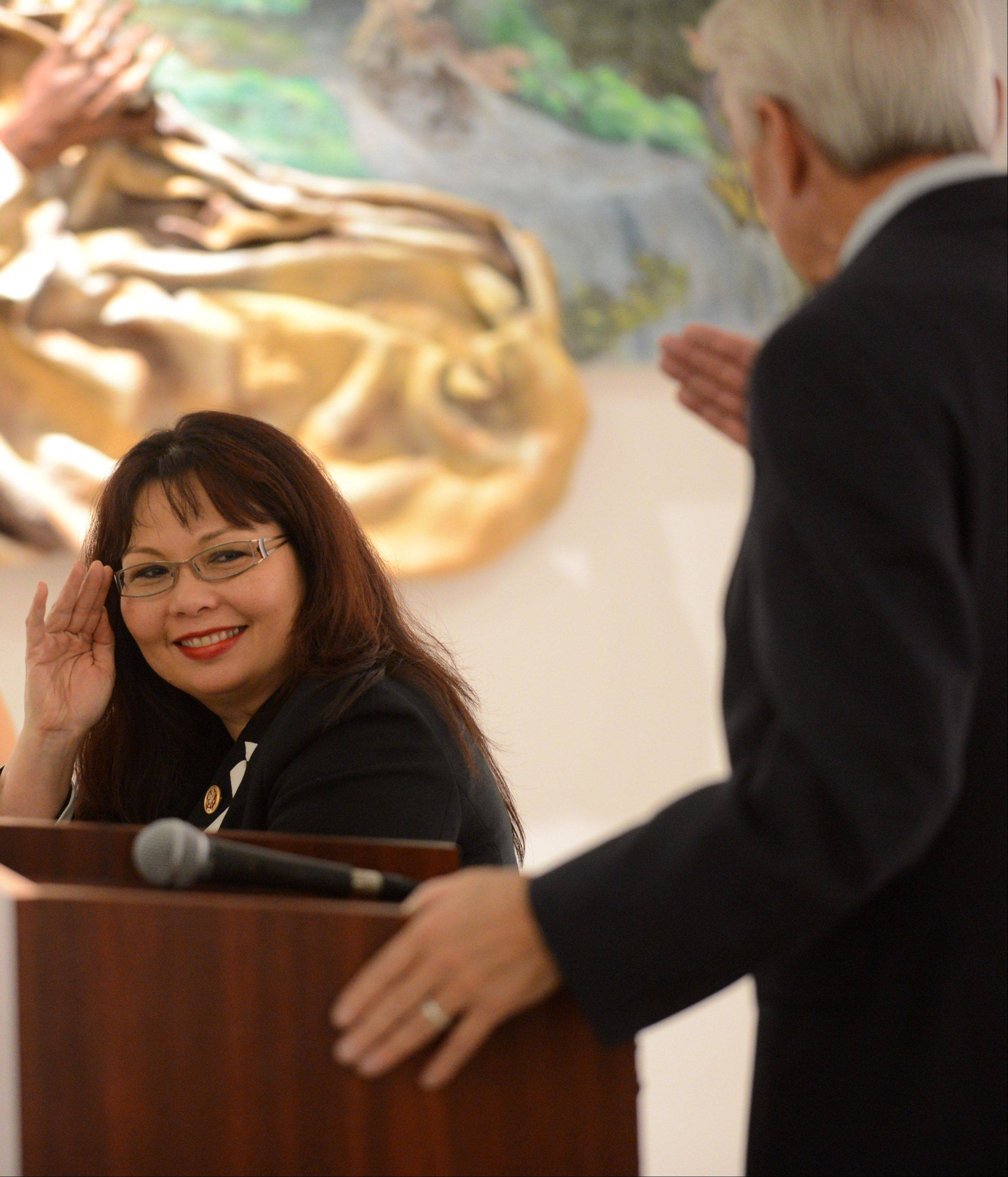 "U.S. Rep. Tammy Duckworth returns a salute from state Rep. Keith Farnham as he speaks during ""Salute to Women Veterans: Past and Present"" Friday at Elgin ArtSpace Lofts."