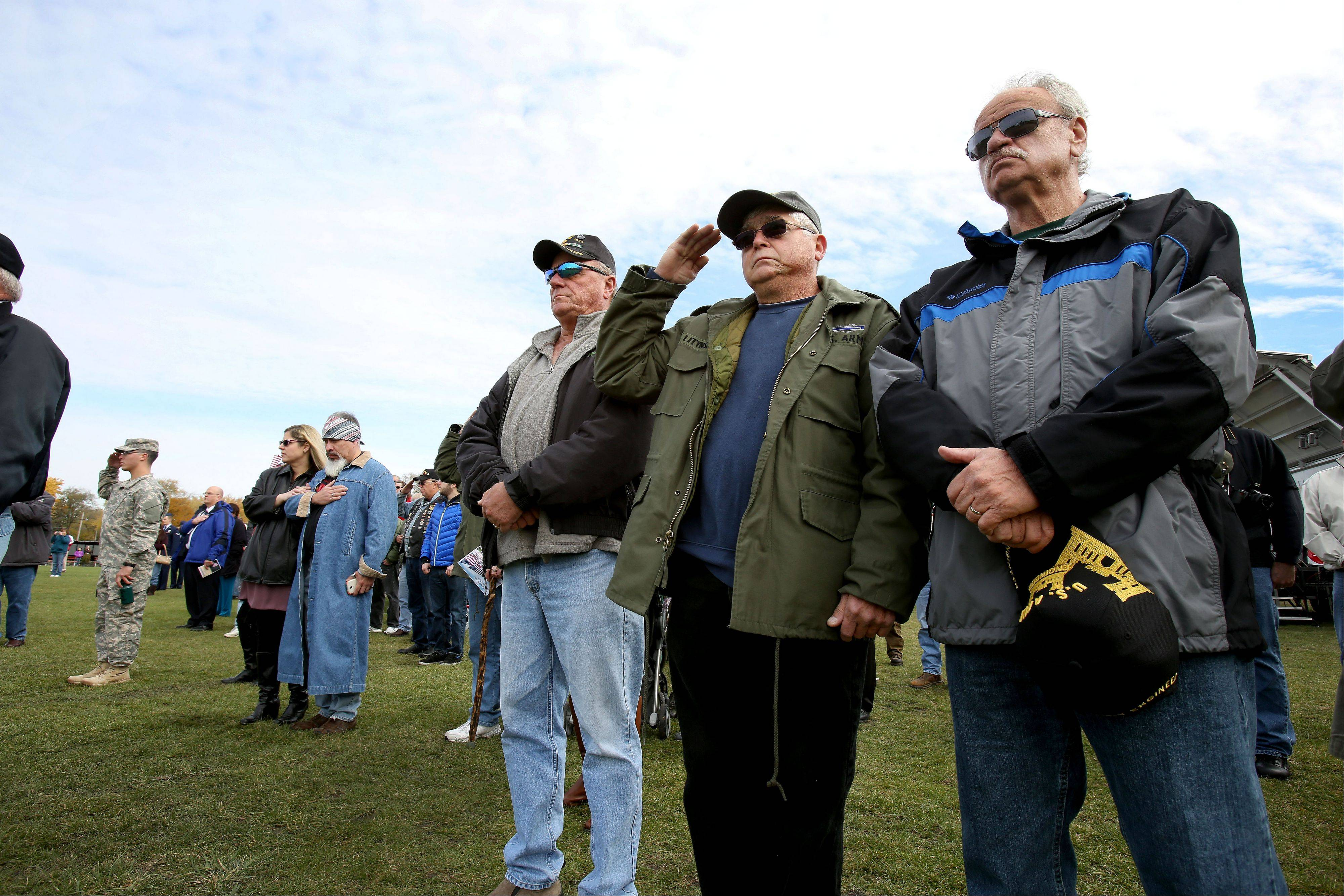 Vietnam veterans Maurie Misner of Montgomery, George Litynski of Bolingbrook and Henry Kostanski of Oswego stand at attention during opening ceremonies for The Moving Wall Friday at West Aurora High School.