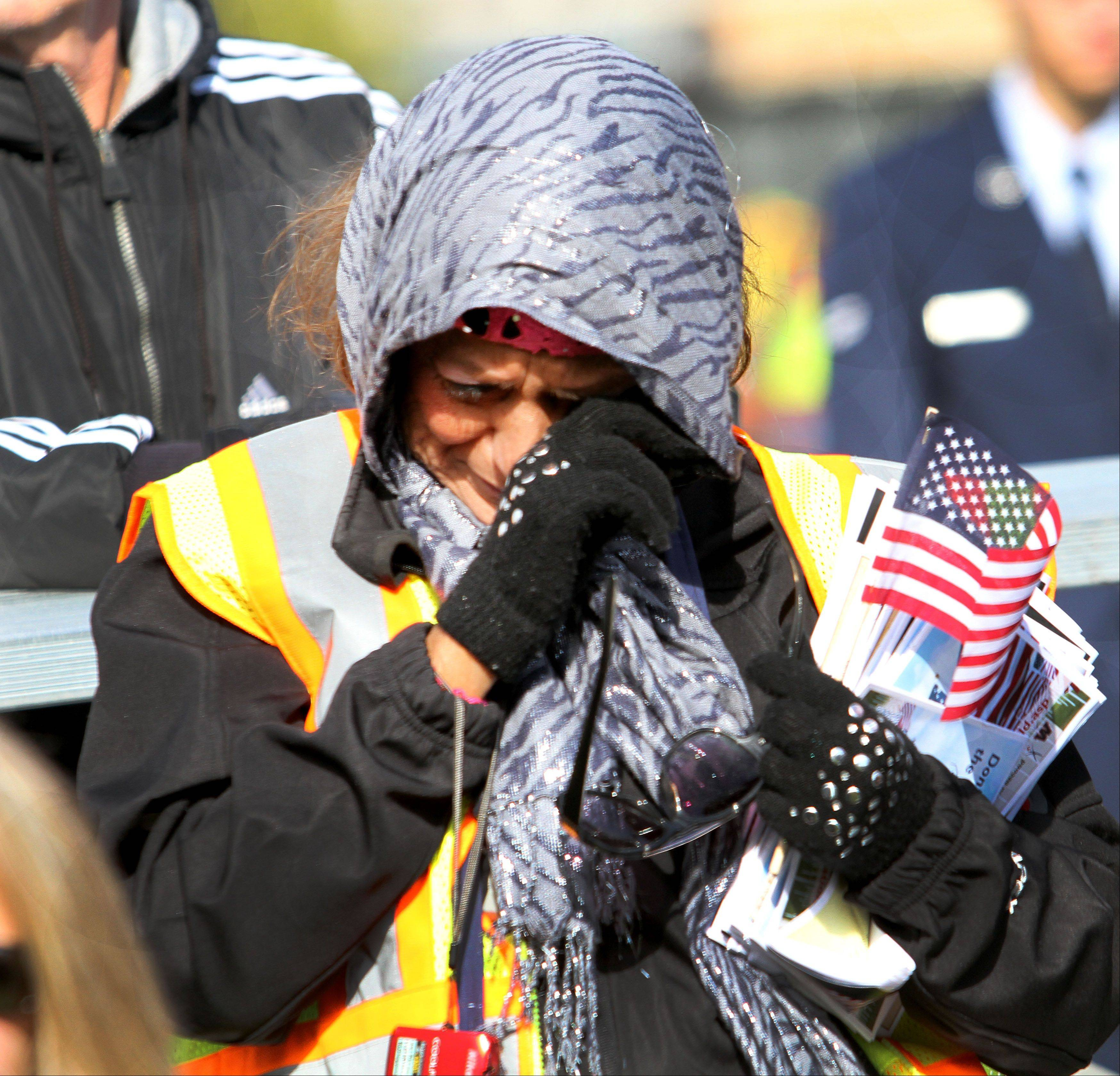 Beda Hernandez, of Oswego, wipes away a tear during the opening ceremonies for The Moving Wall Friday at West Aurora High School.