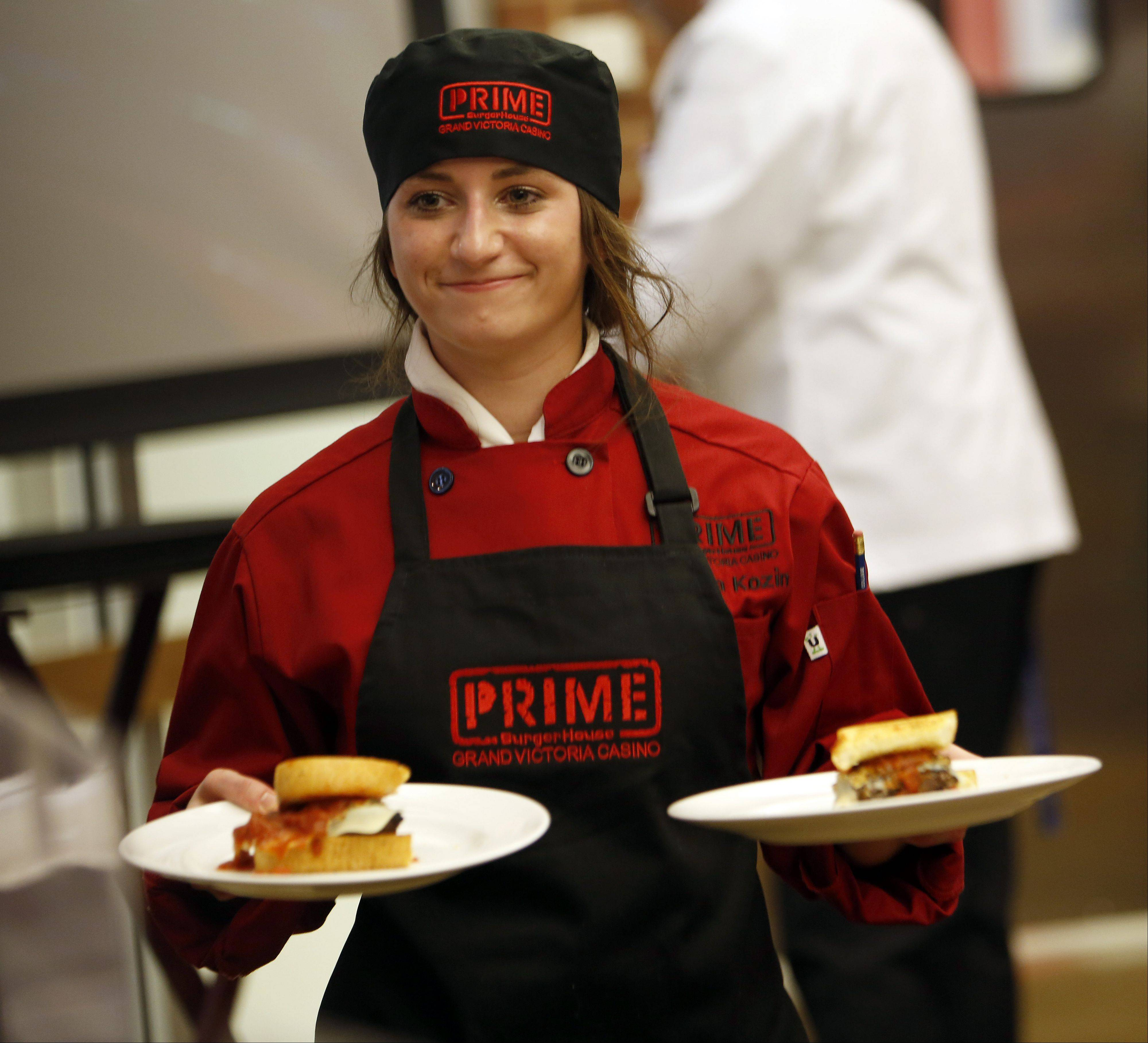Sabrina Kozin of Huntley delivers her Lasagna Burger to the judges at Elgin Community College's fifth annual ECC-Prime BurgerHouse Burger Competition Friday at the Spartan Terrace Restaurant in Elgin.